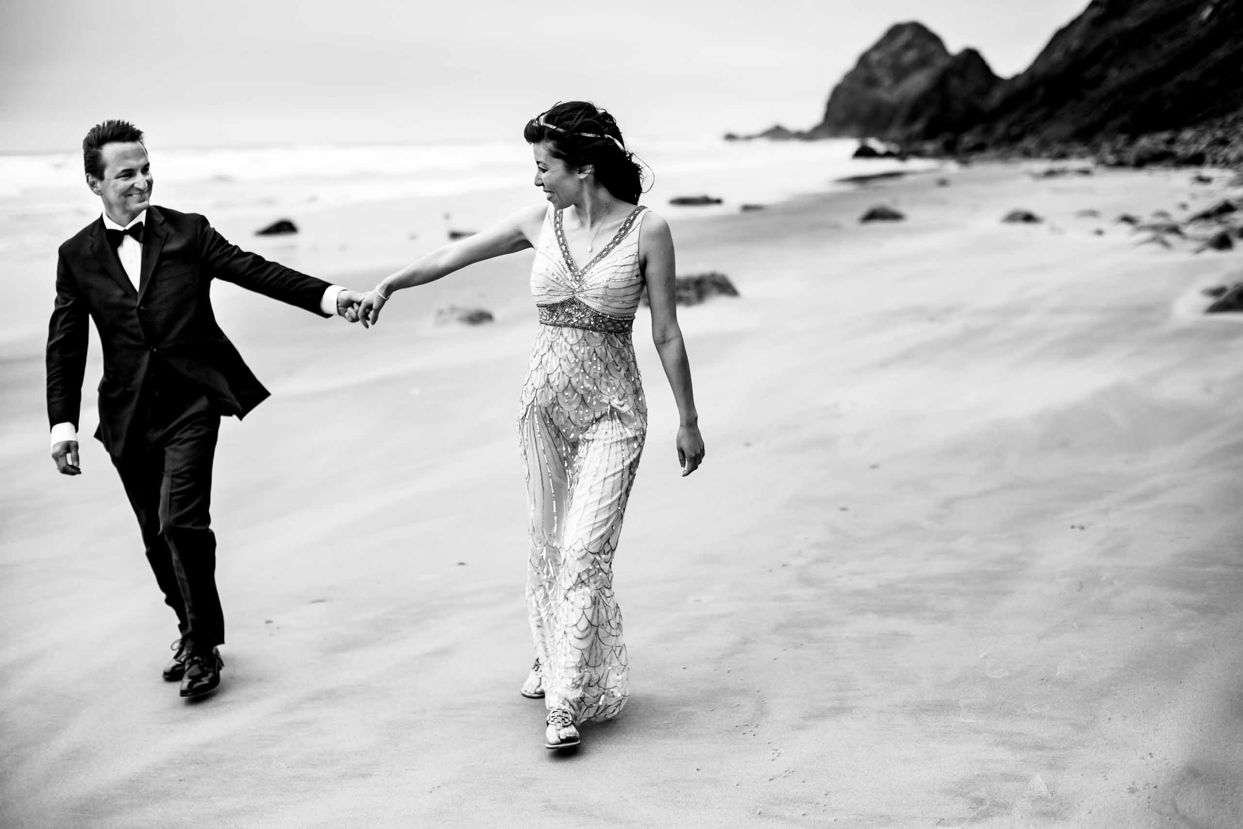Bride and groom walking down the beach during their Manzanita Elopement