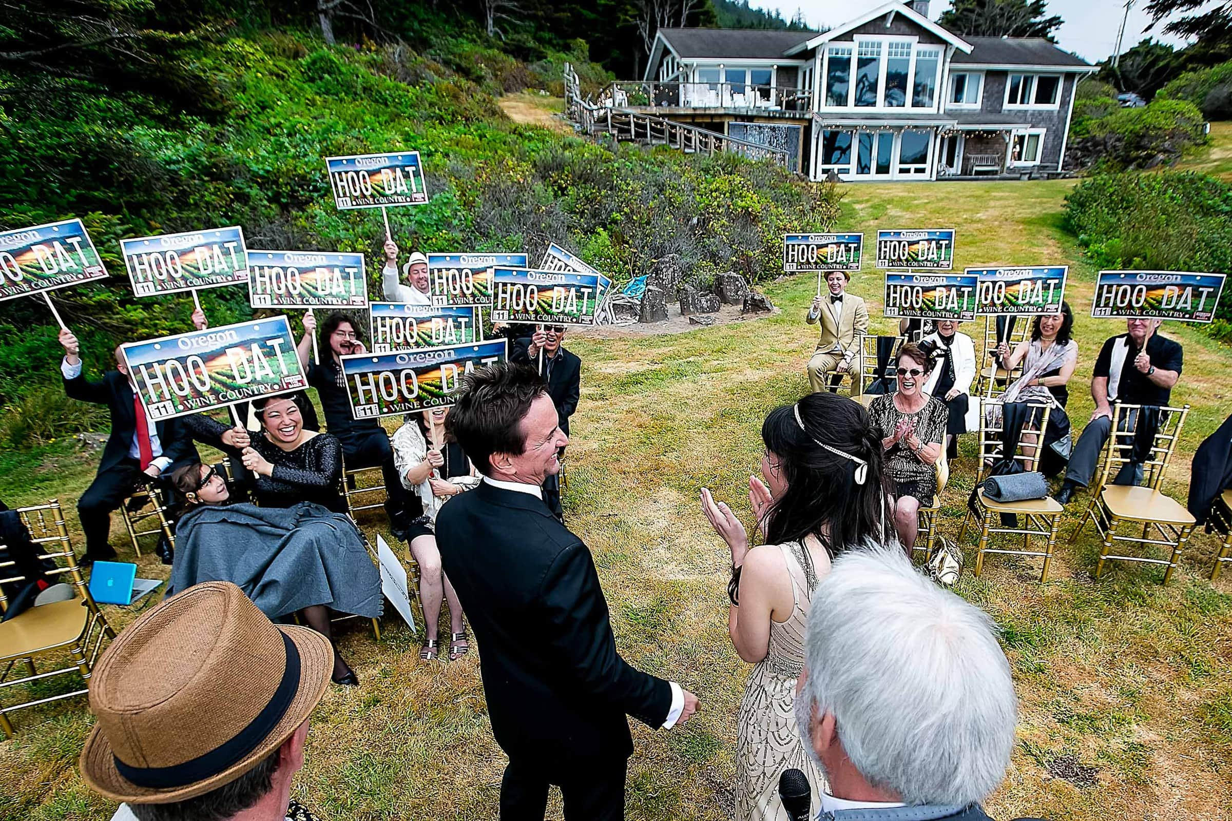 Fun Manzanita elopement ceremony photo of bride and groom laughing with guests holding up New Orleans HOO DAT signs