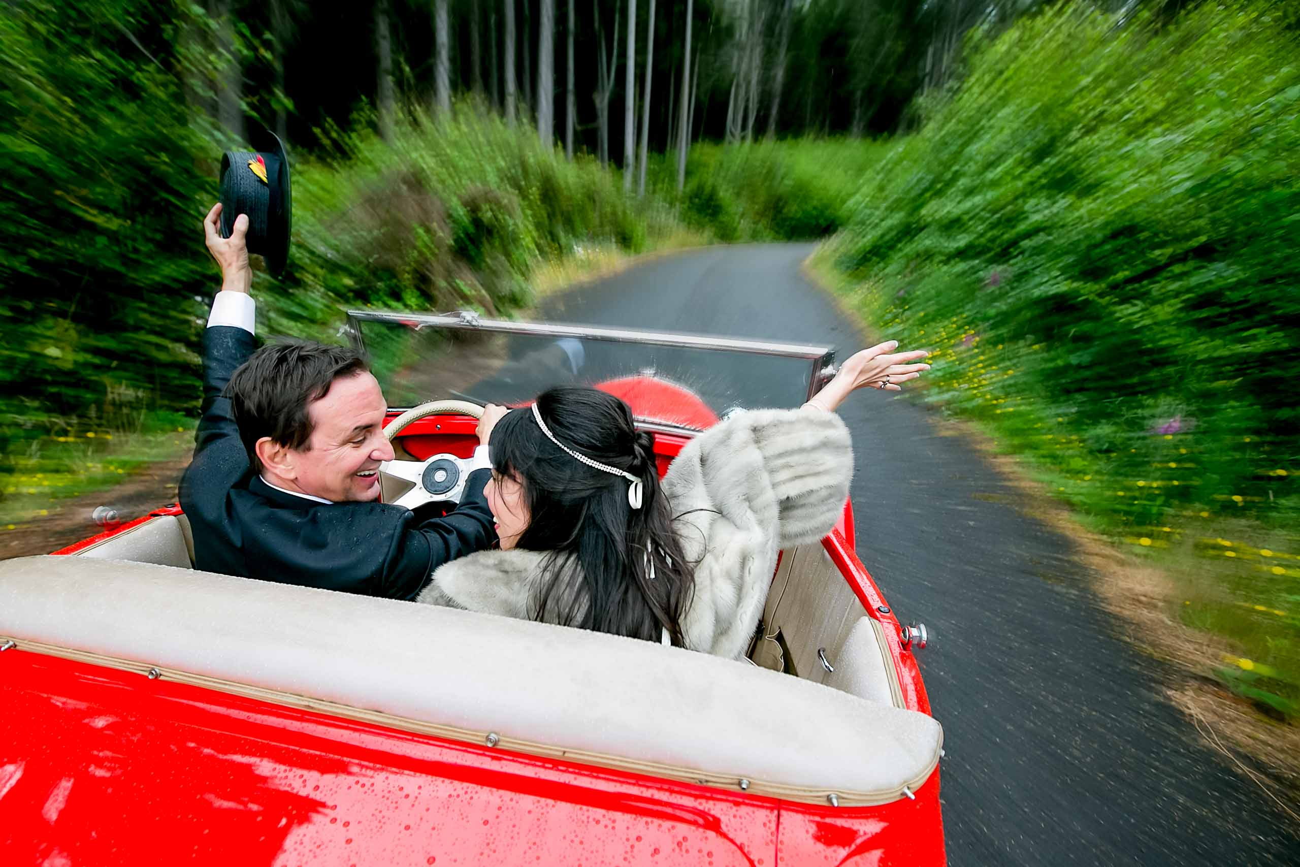 Bride and groom riding a roadster through the woods during their Manzanita elopement in Oregon