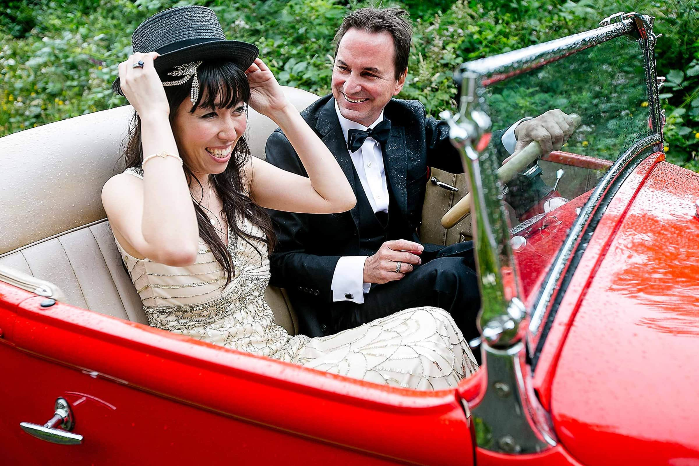Bride and groom riding a roadster with fun hats during their Manzanita elopement in Oregon