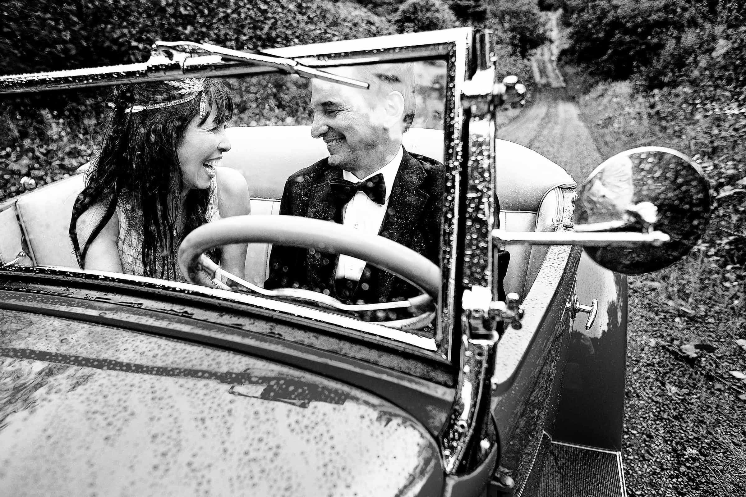 Bride and groom laughing together in a roadster during their Manzanita elopement in Oregon