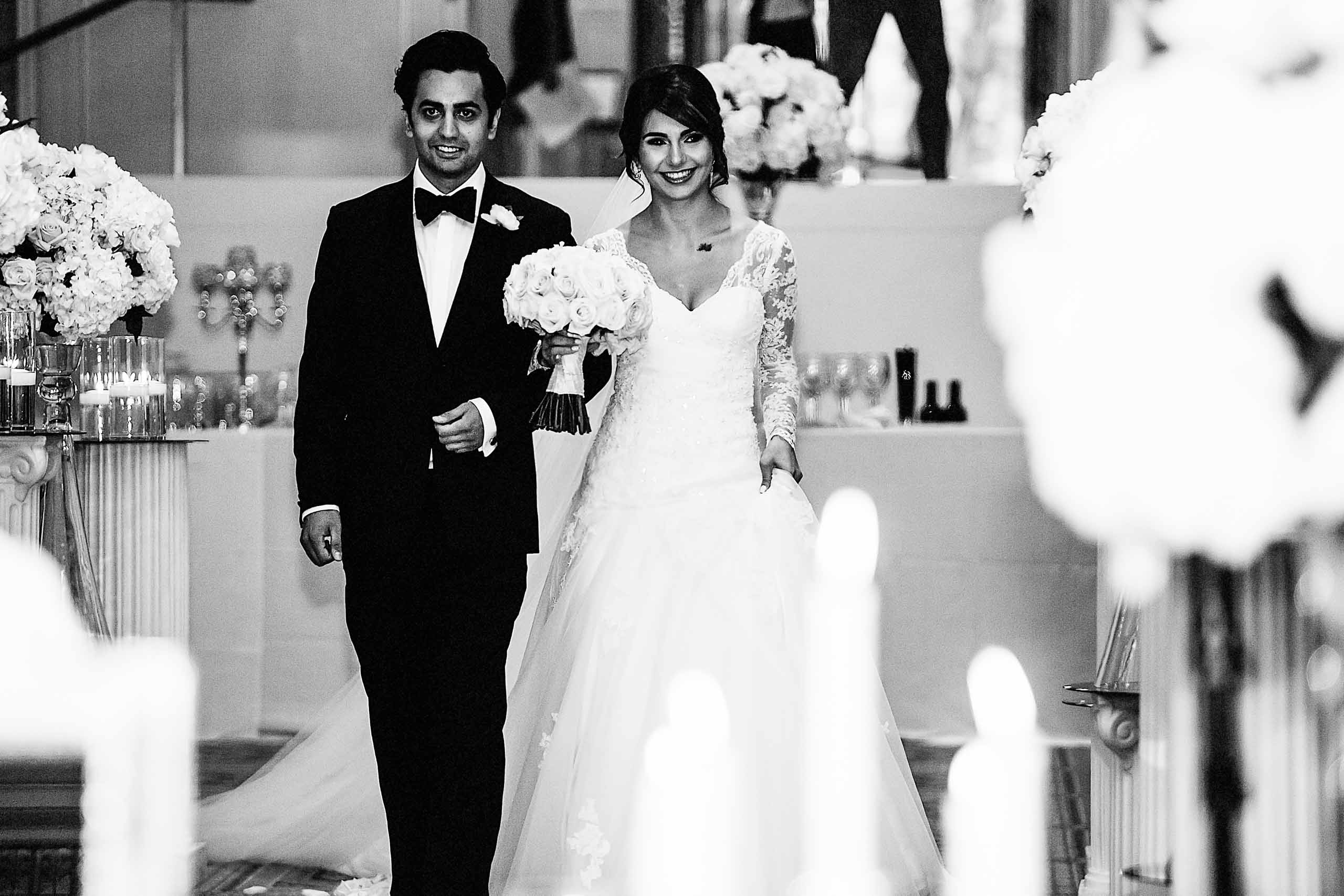A bride and groom walking into their Portland Persian wedding ceremony at the Portland Art Museum