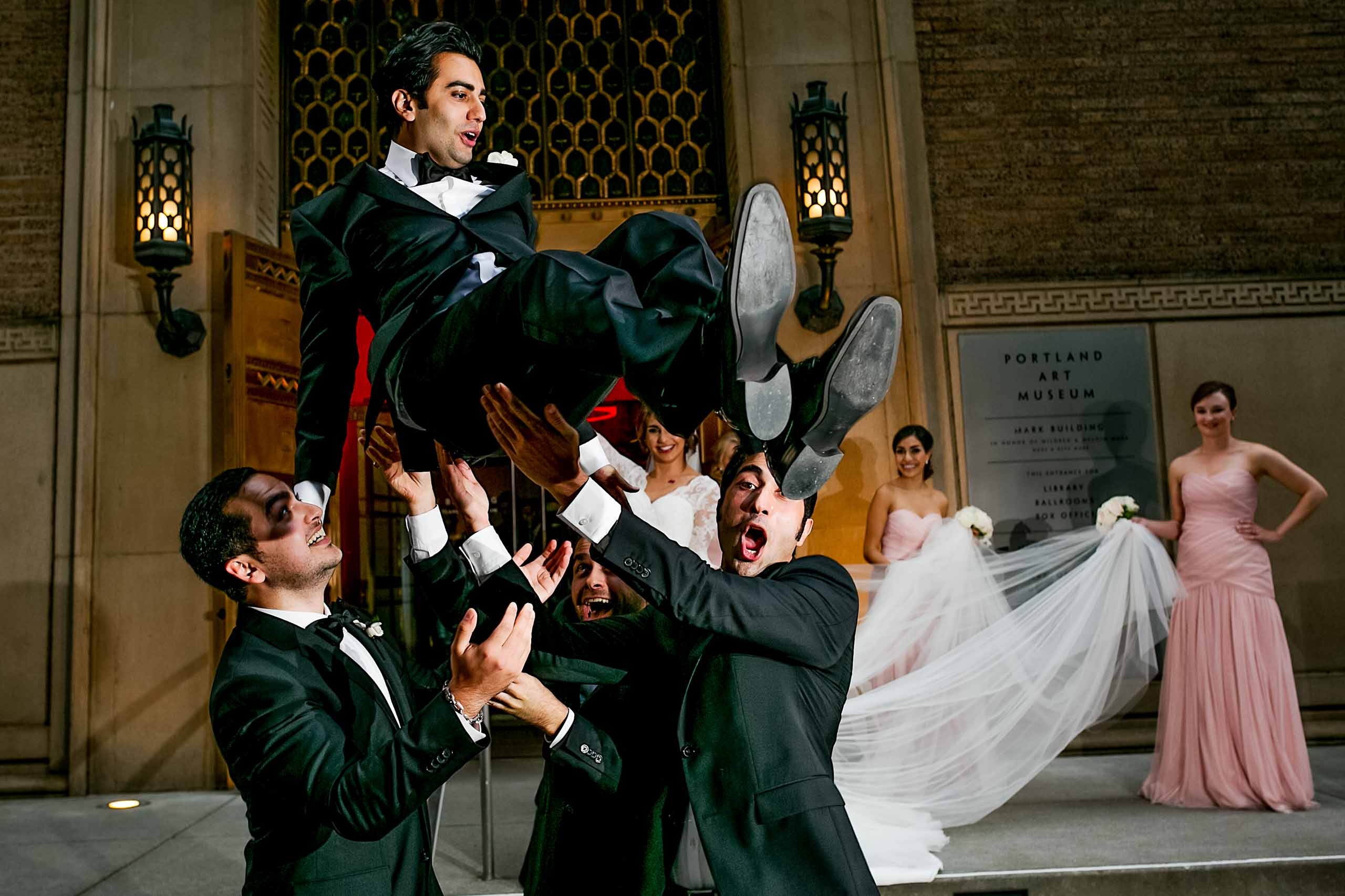 A groom being thrown into the air by his best friends moments after his Portland Persian wedding at the Portland Art Museum