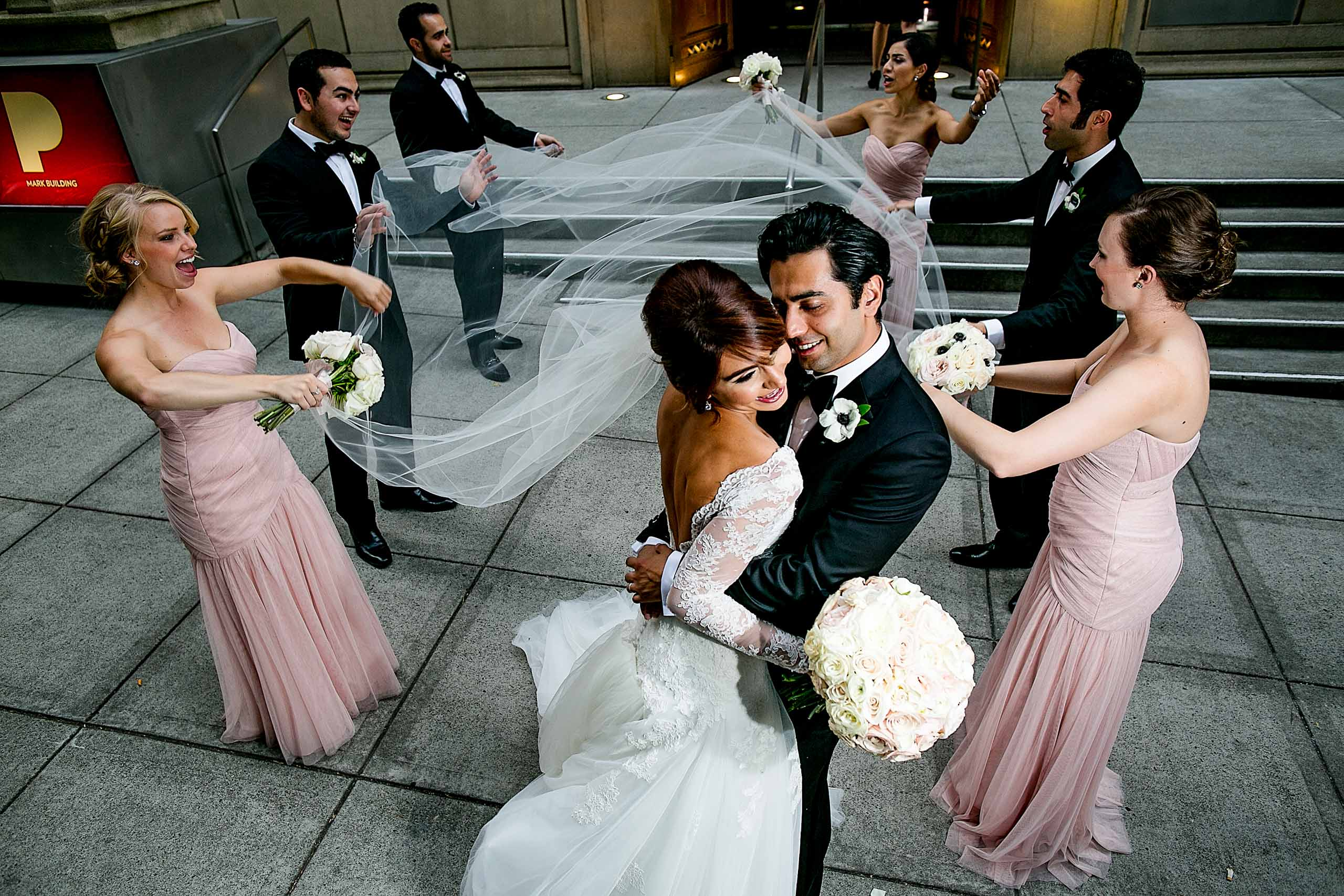 A groom and bride embracing each other while surrounded by best friends during their Portland Persian wedding at the Portland Art Museum