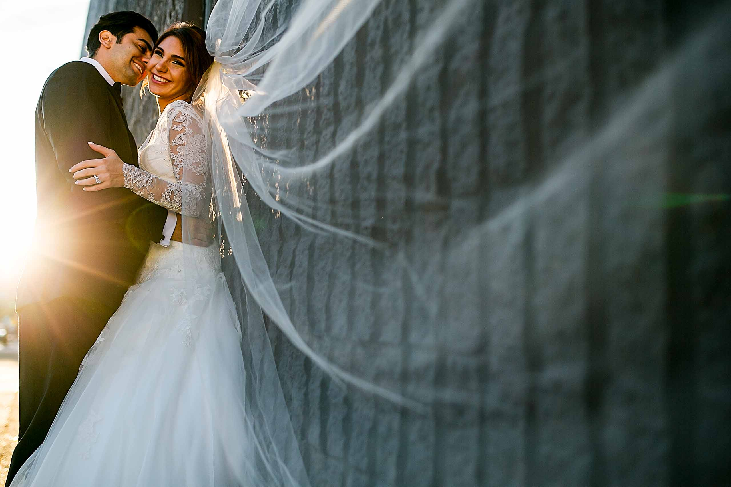 A warm sun flare photo of a bride and groom embracing near a stone wall during golden hour for their Portland Persian wedding at the Portland Art Museum