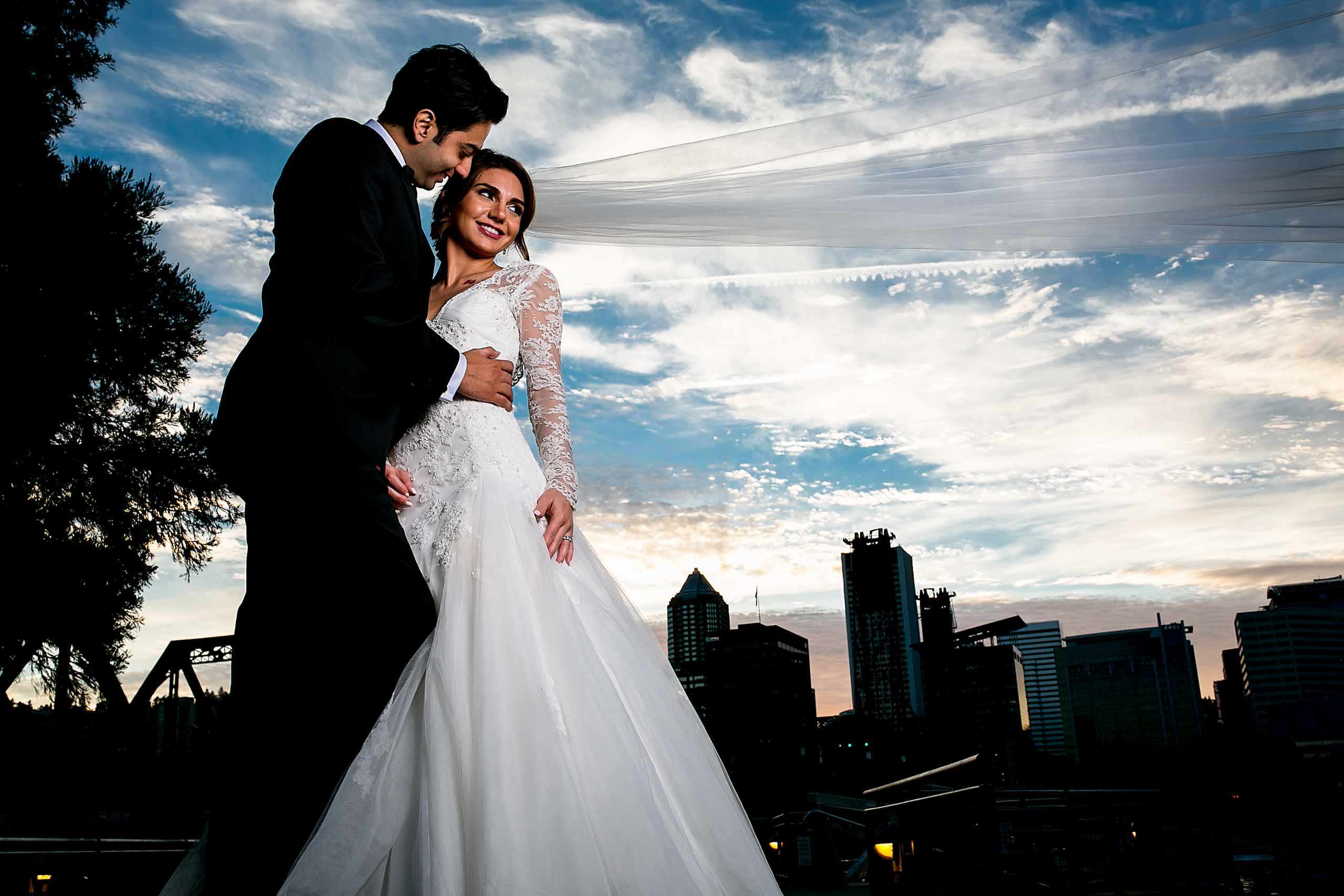 Silhouette photo of Portland cityscape with a bride and groom beautifully lit up during their Portland Persian wedding at the Portland Art Museum