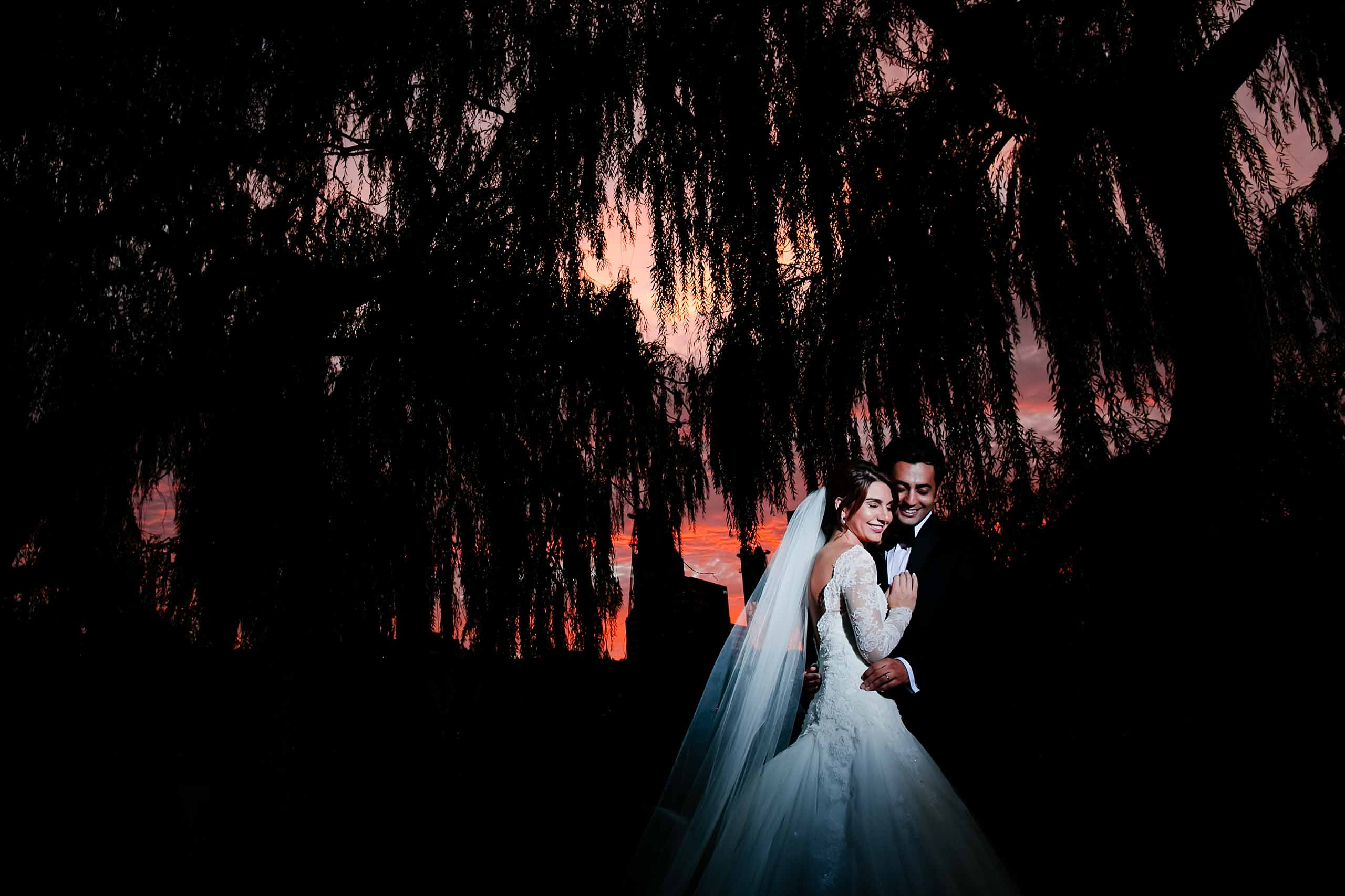 Sunset photo of Portland waterfront and trees with a bride and groom beautifully lit up during their Portland Persian wedding at the Portland Art Museum