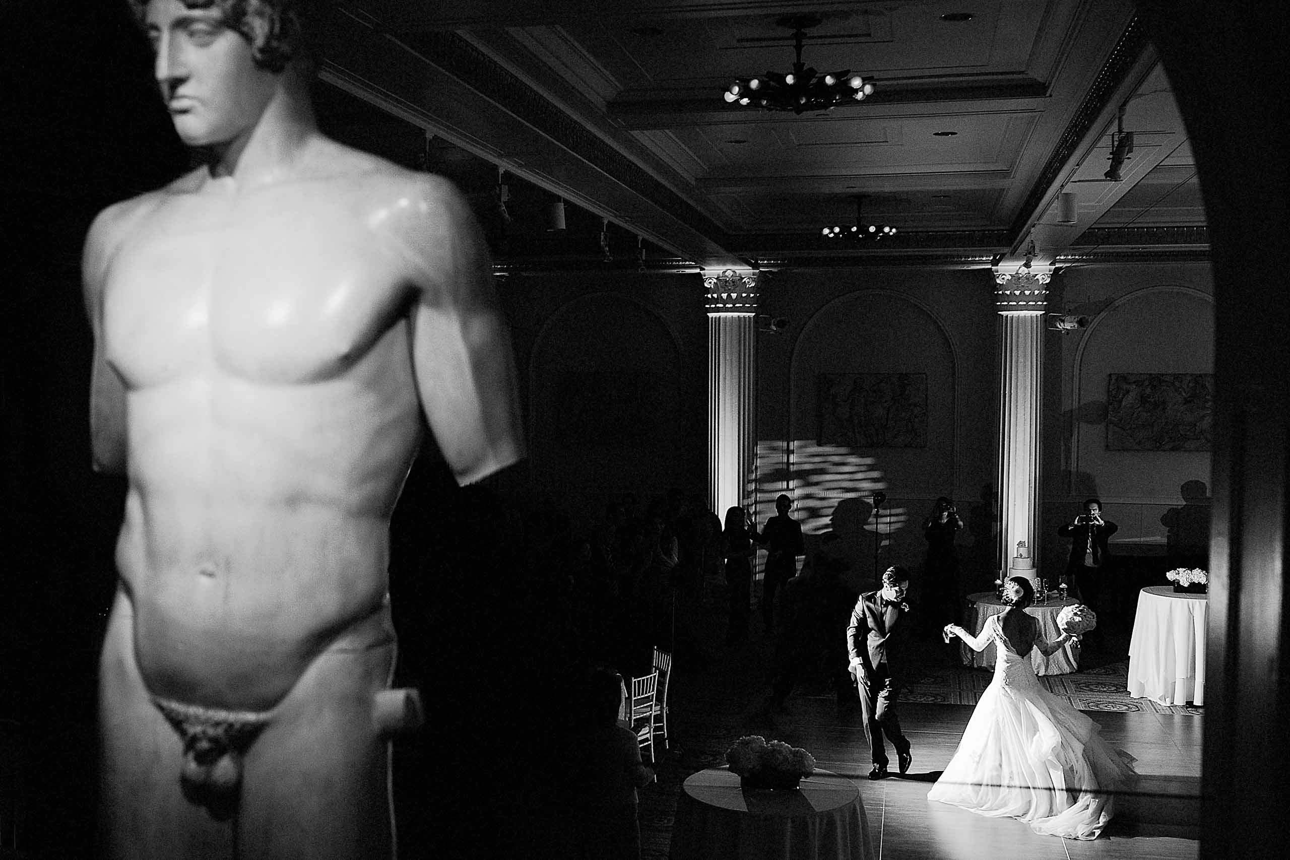 A first dance photo of a Persian bride and groom surrounded by statues during their Portland Persian wedding at the Portland Art Museum