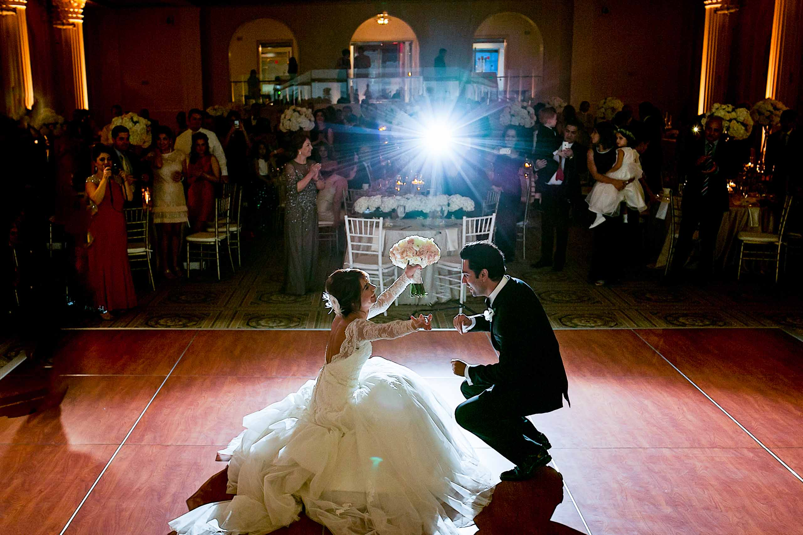 A first dance photo of a Persian bride dipping down low with the groom during their Portland Persian wedding at the Portland Art Museum reception