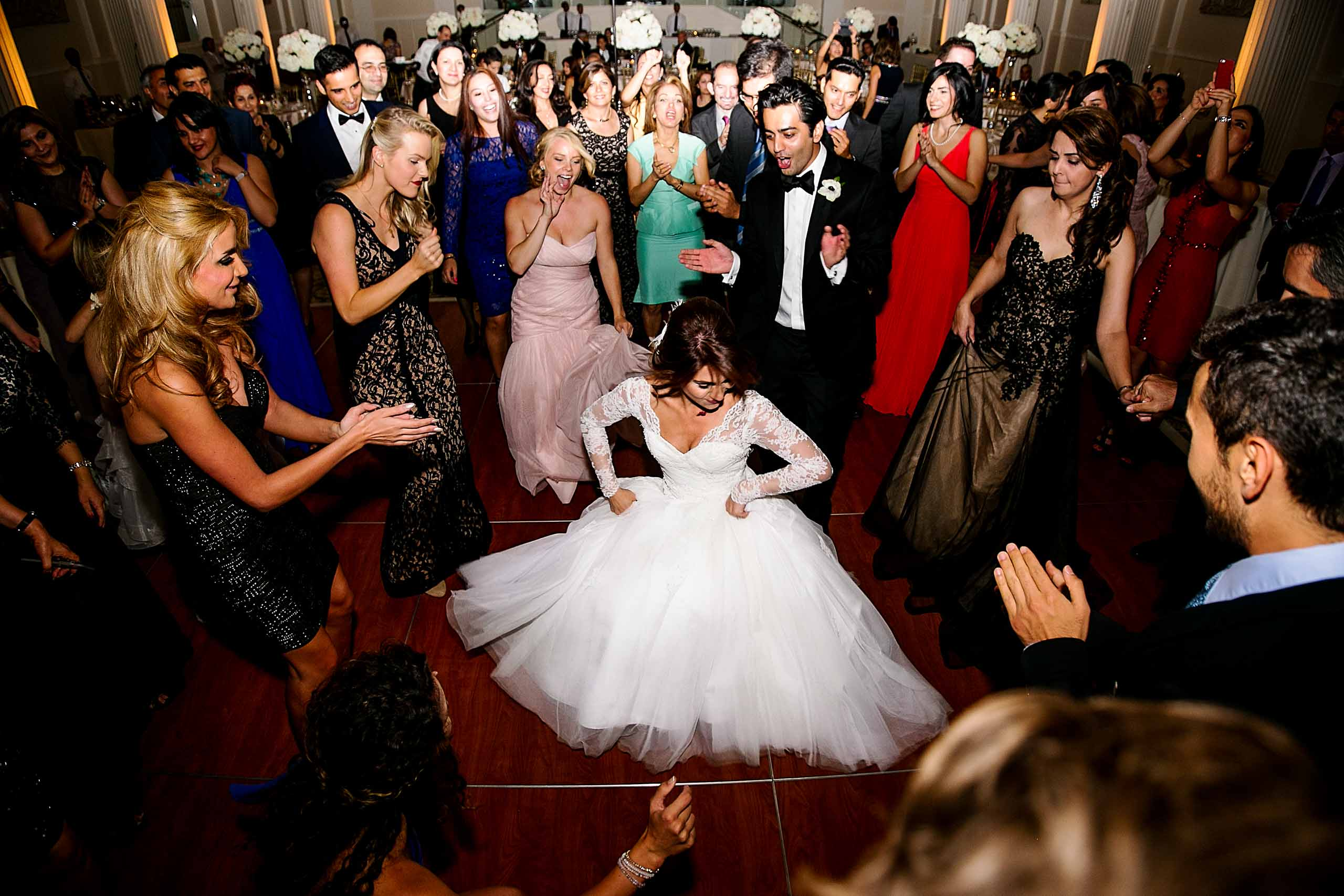A fun and wild dance photo of a Persian bride dipping down low during a Portland Persian wedding at the Portland Art Museum reception