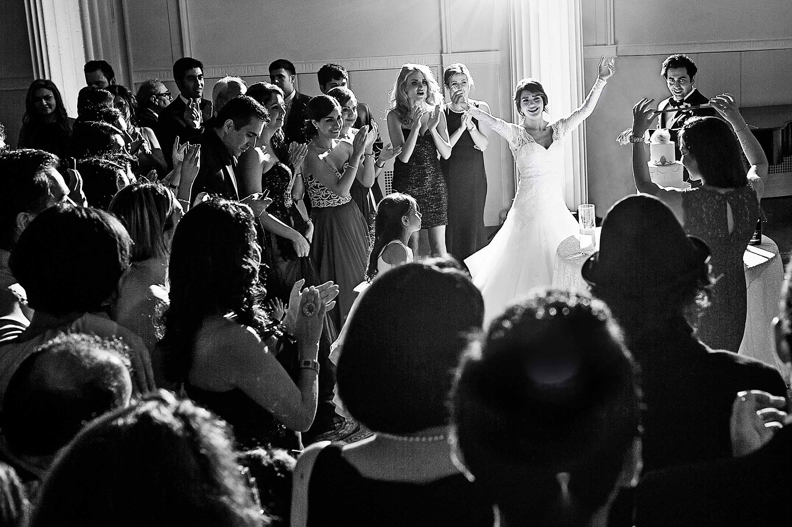 A bride doing a Persian knife dance near the cake during a Portland Persian wedding at the Portland Art Museum