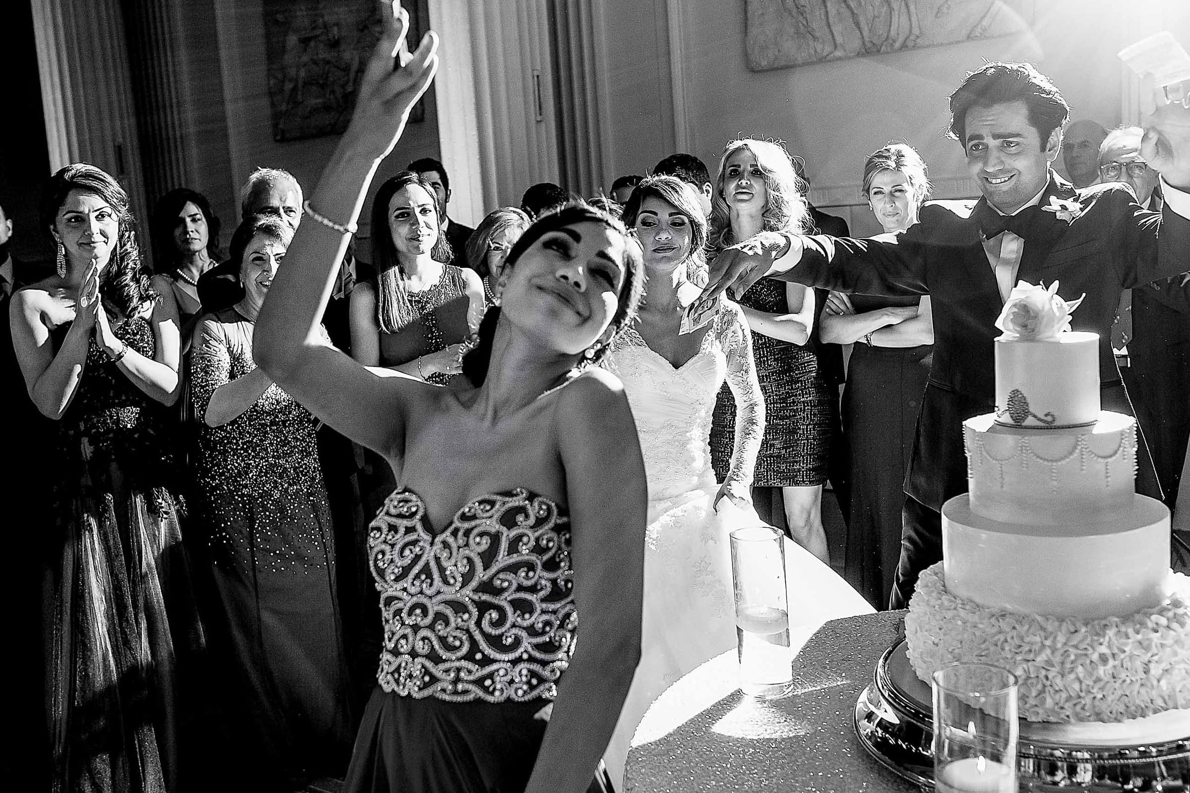 The sister of the bride doing a Persian knife dance near the cake to the groom during a Portland Persian wedding at the Portland Art Museum