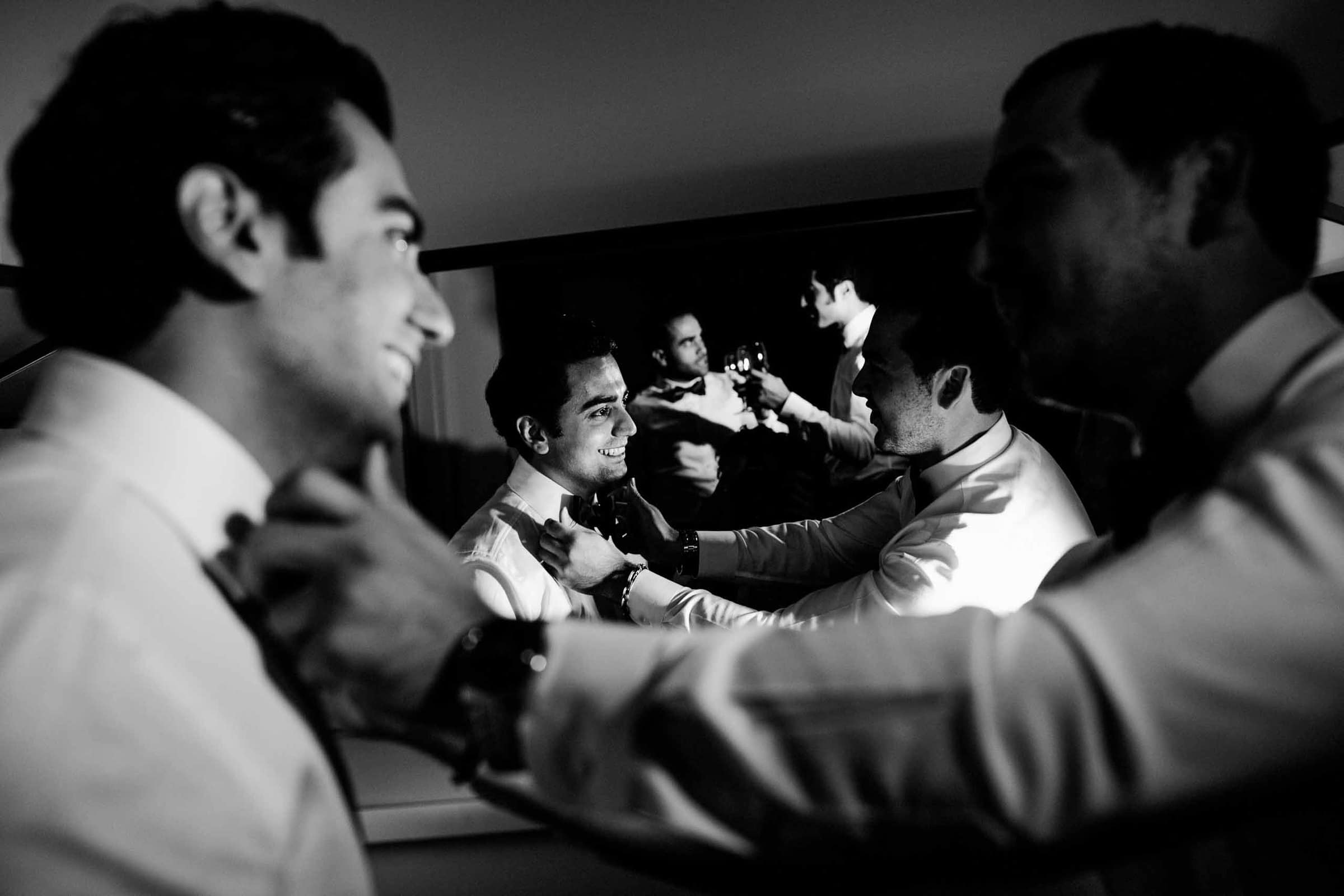 A layering story telling photo of a groom and his best friends getting ready for his Portland Persian wedding at the Portland Art Museum in Portland's Park Blocks
