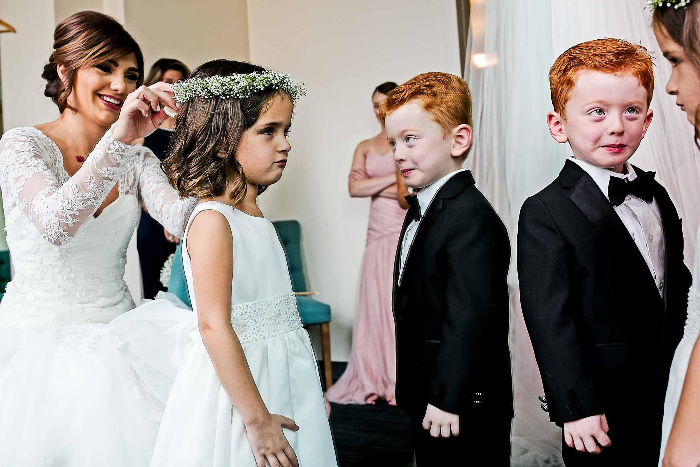 A story telling photo of a bride and children getting ready in mirror reflections for her Portland Persian wedding at the Portland Art Museum in Portland's Park Blocks