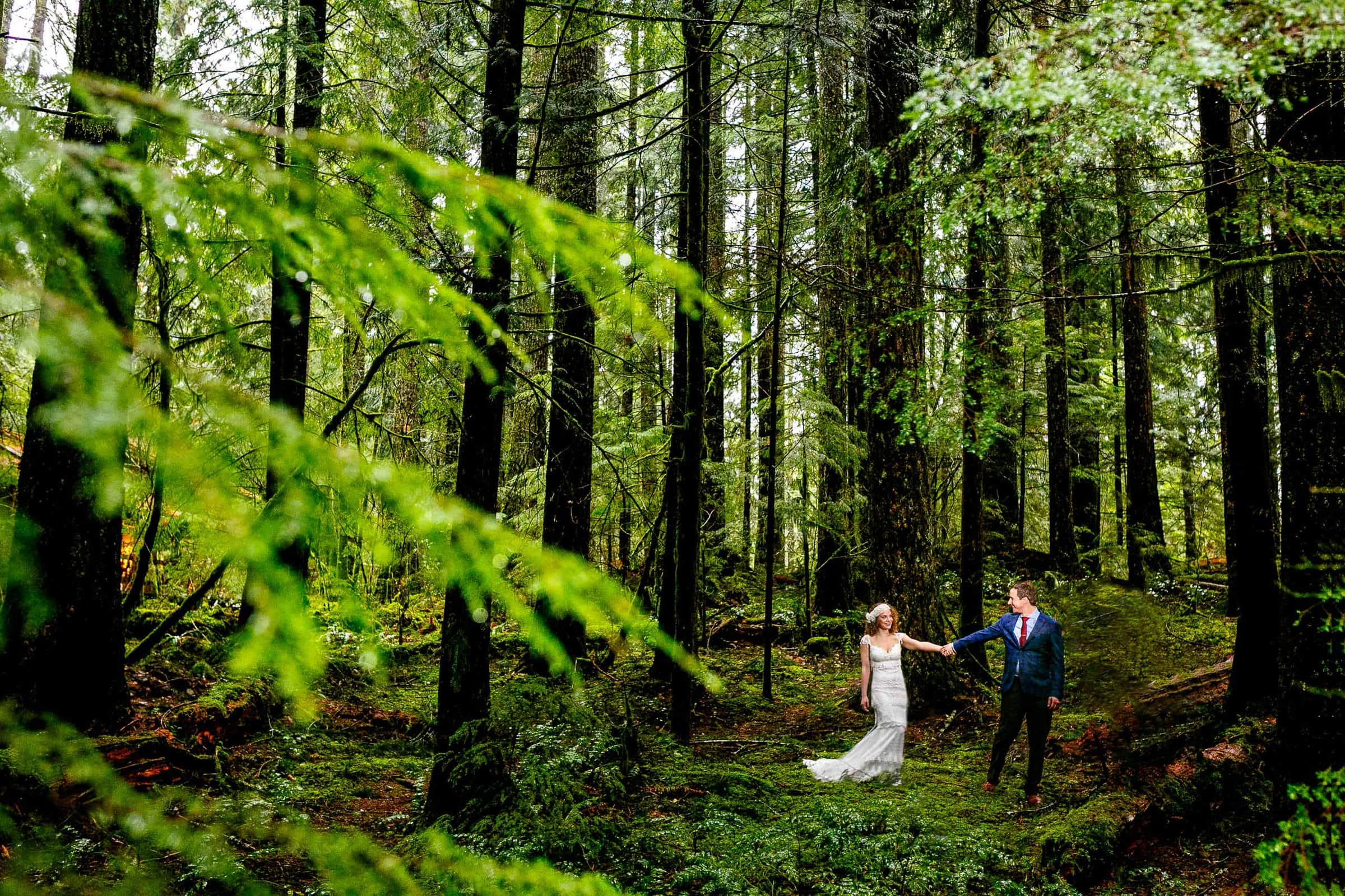 Bride and groom walking with each other in the woods in Government Camp before their Silcox Hut Wedding above Timberline Lodge on Mt Hood.