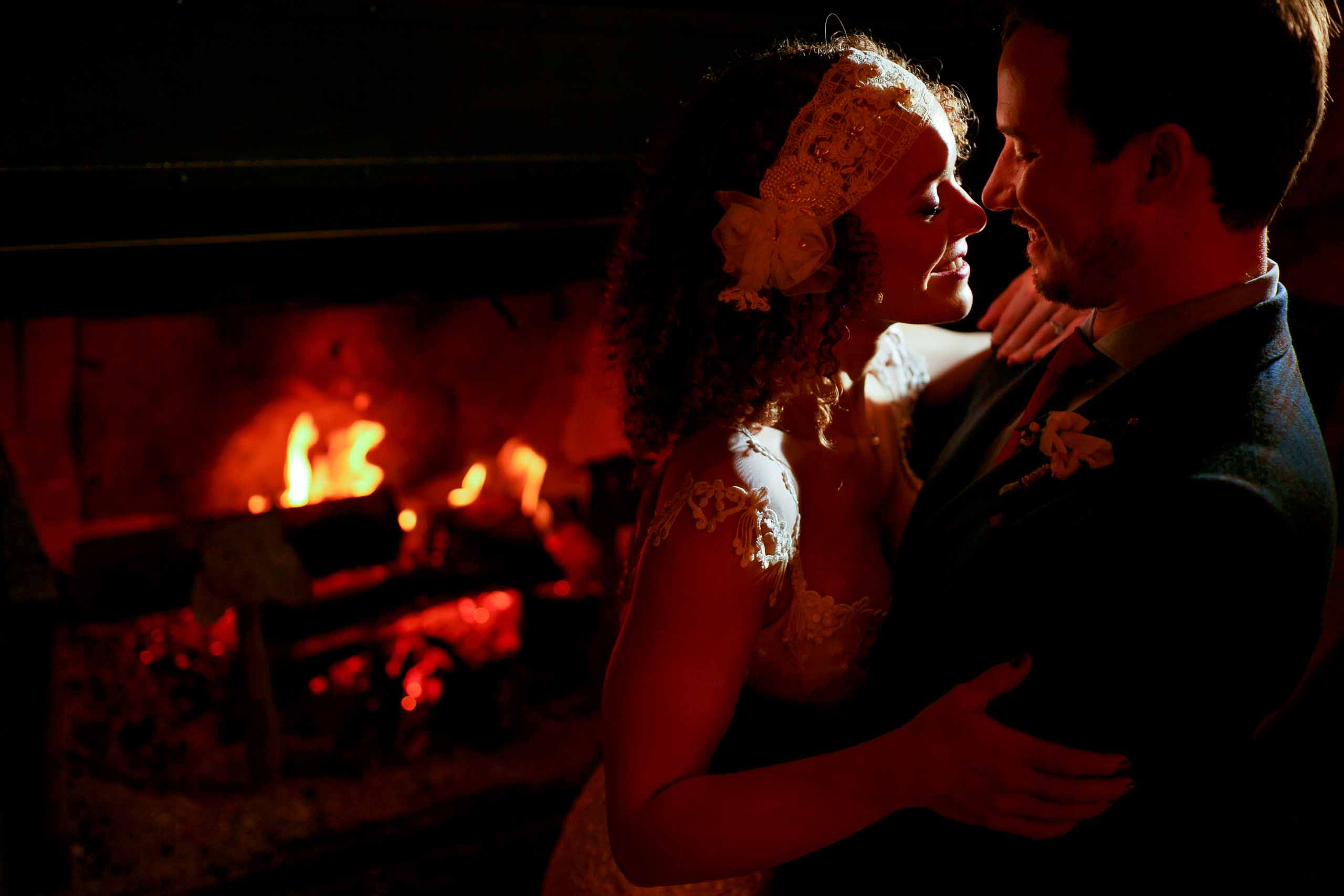 Intimate photo of bride and groom holding each other near the fire moments after their Silcox Hut wedding on Mt Hood above Timberline lodge.