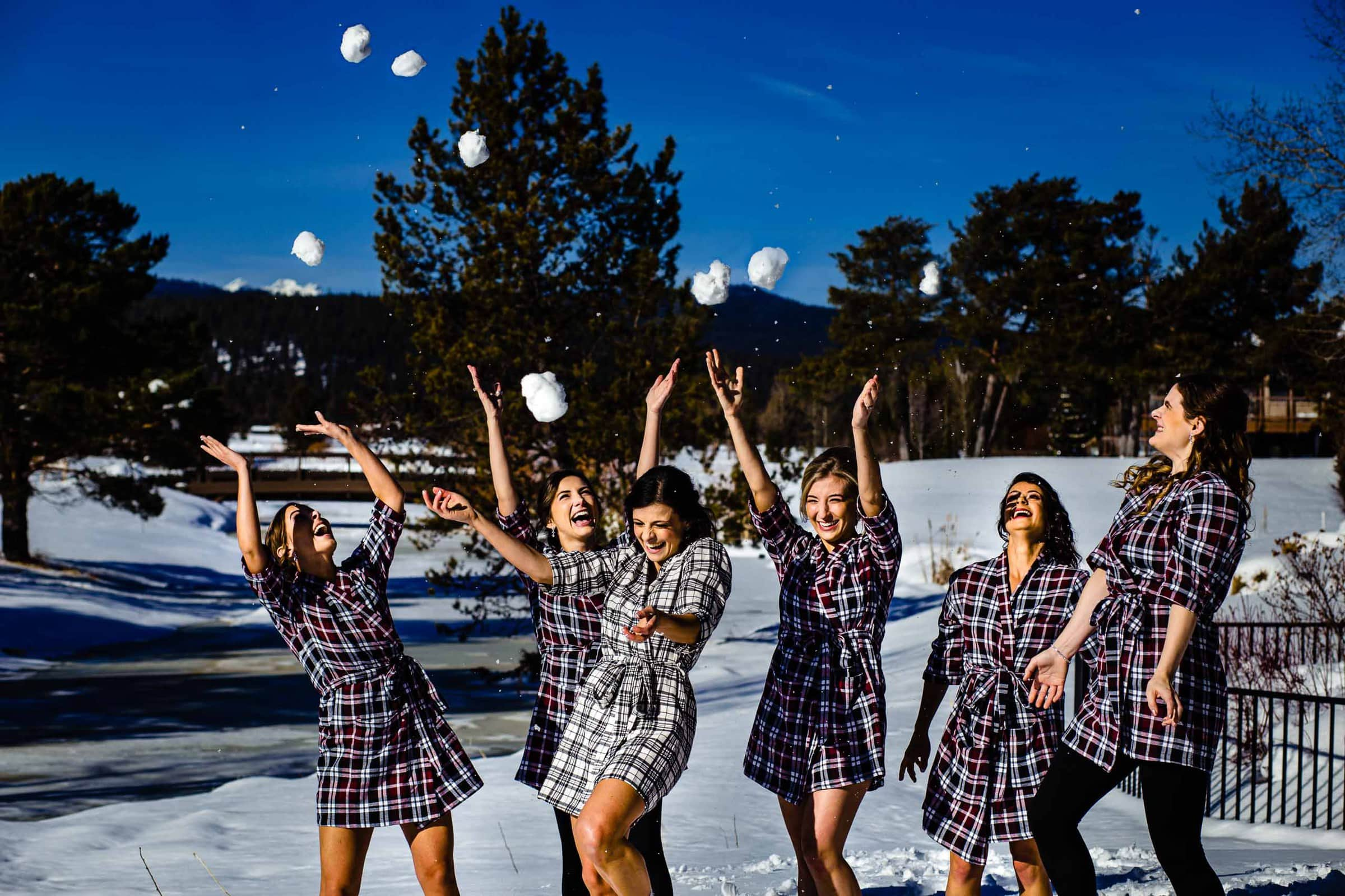 Super fun creative photo of bride mades playing with snowballs at a Sunriver resort wedding