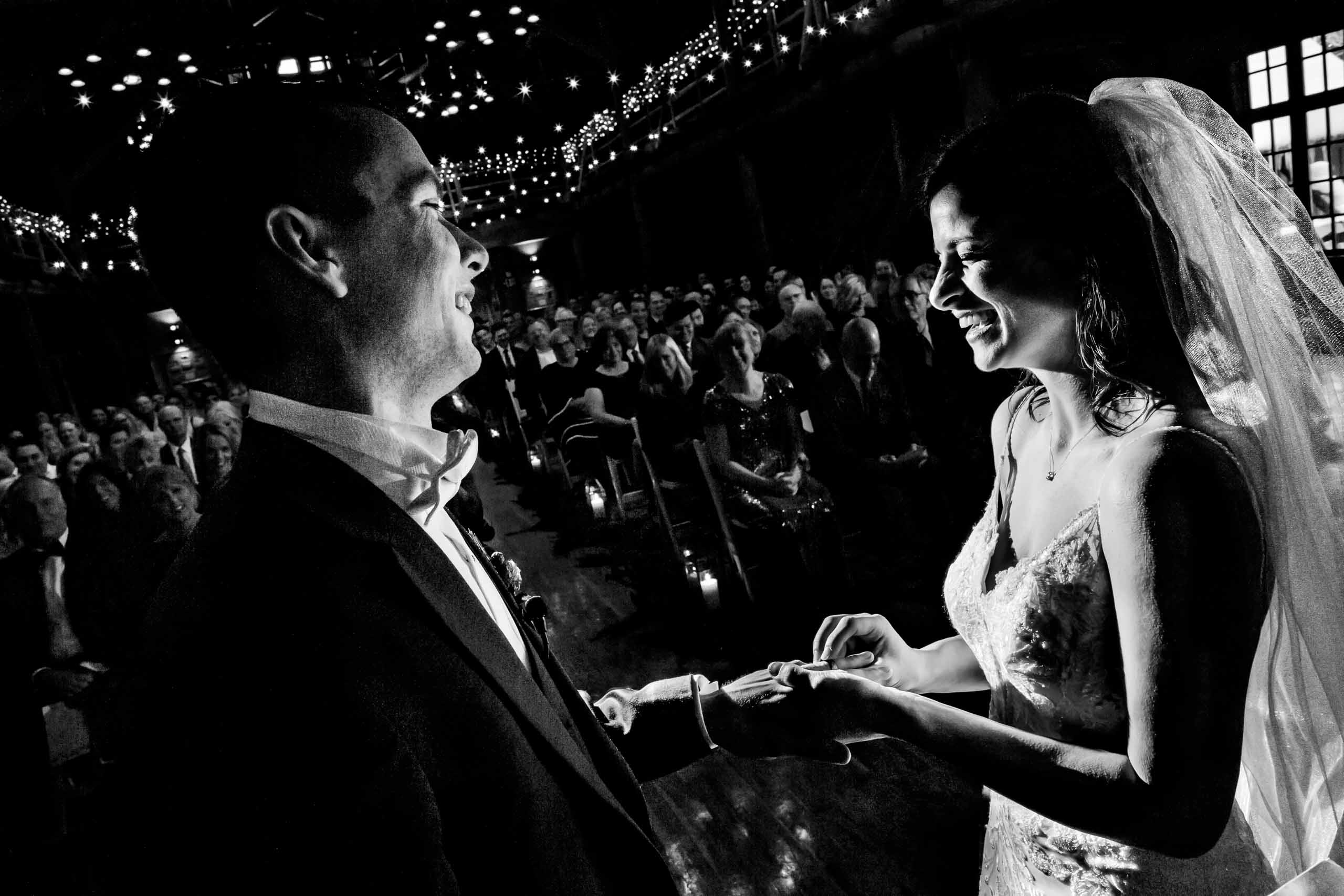 Beautiful photo of bride and groom putting on rings during their Sunriver Resort wedding in Oregon