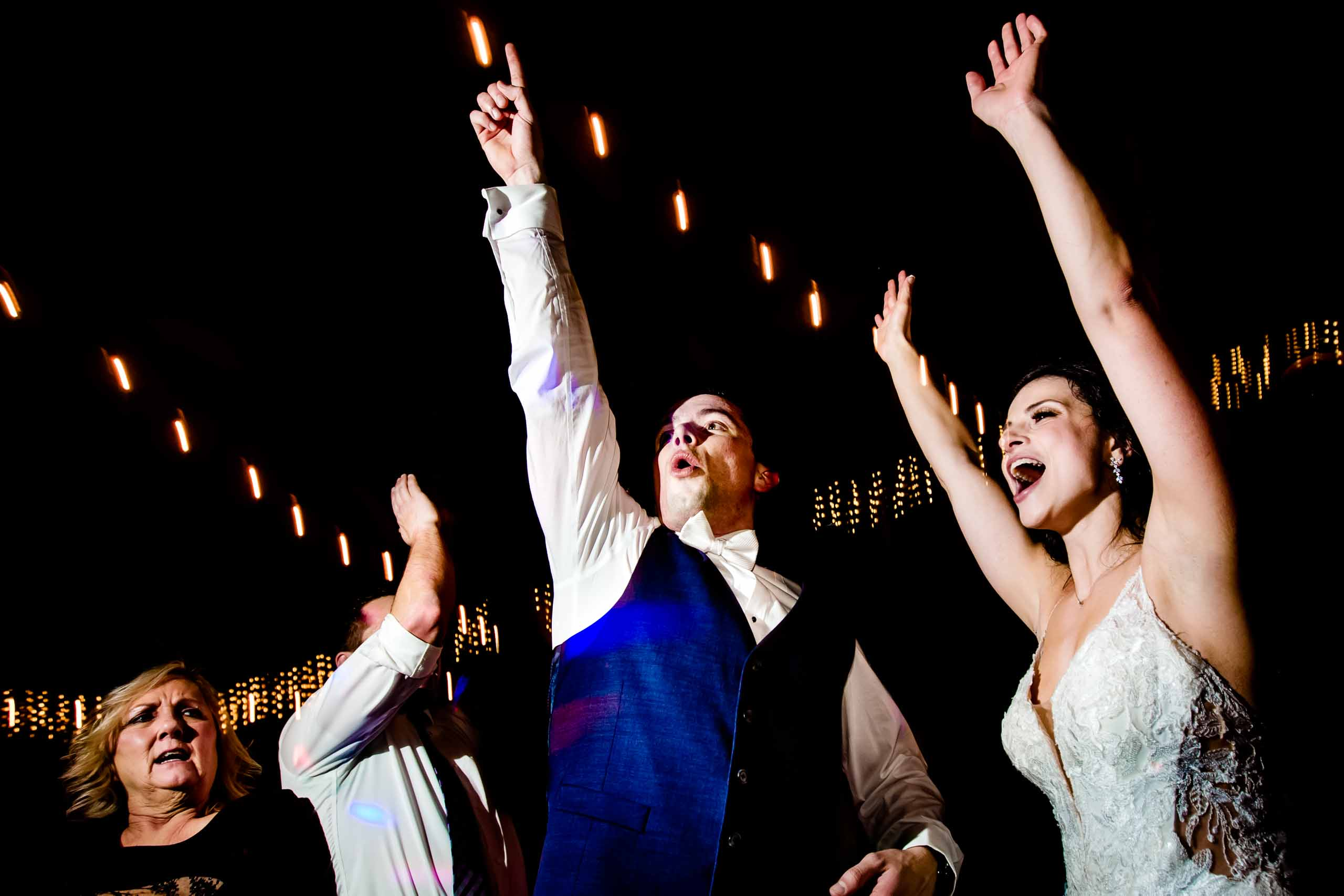 Super fun photo of a bride and groom jumping during their Sunriver Resort wedding reception in Oregon