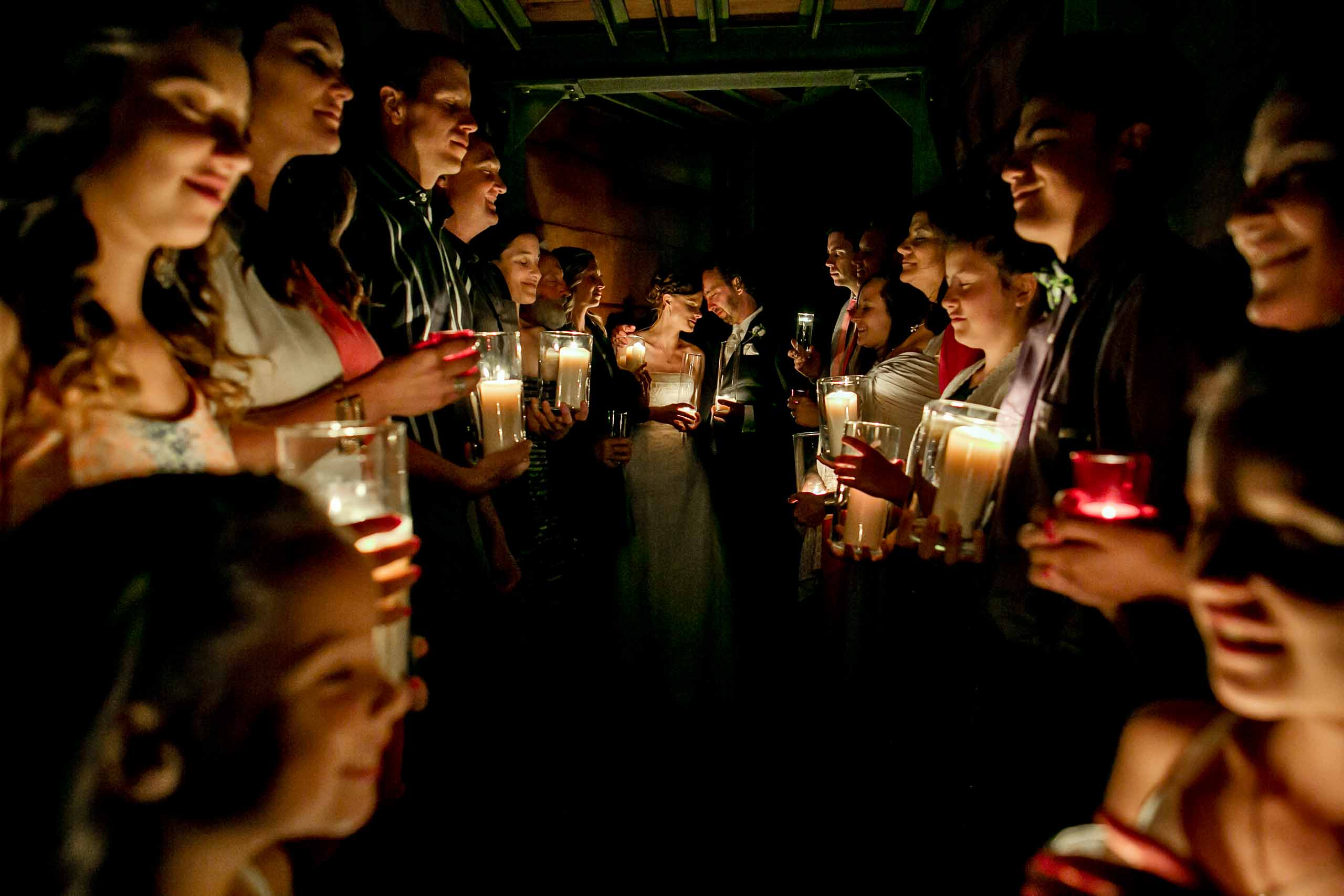 Bride and Groom in an intimate gathering surrounded by candles with family and friends in Silcox Hut atop Mt Hood above Timberline Lodge