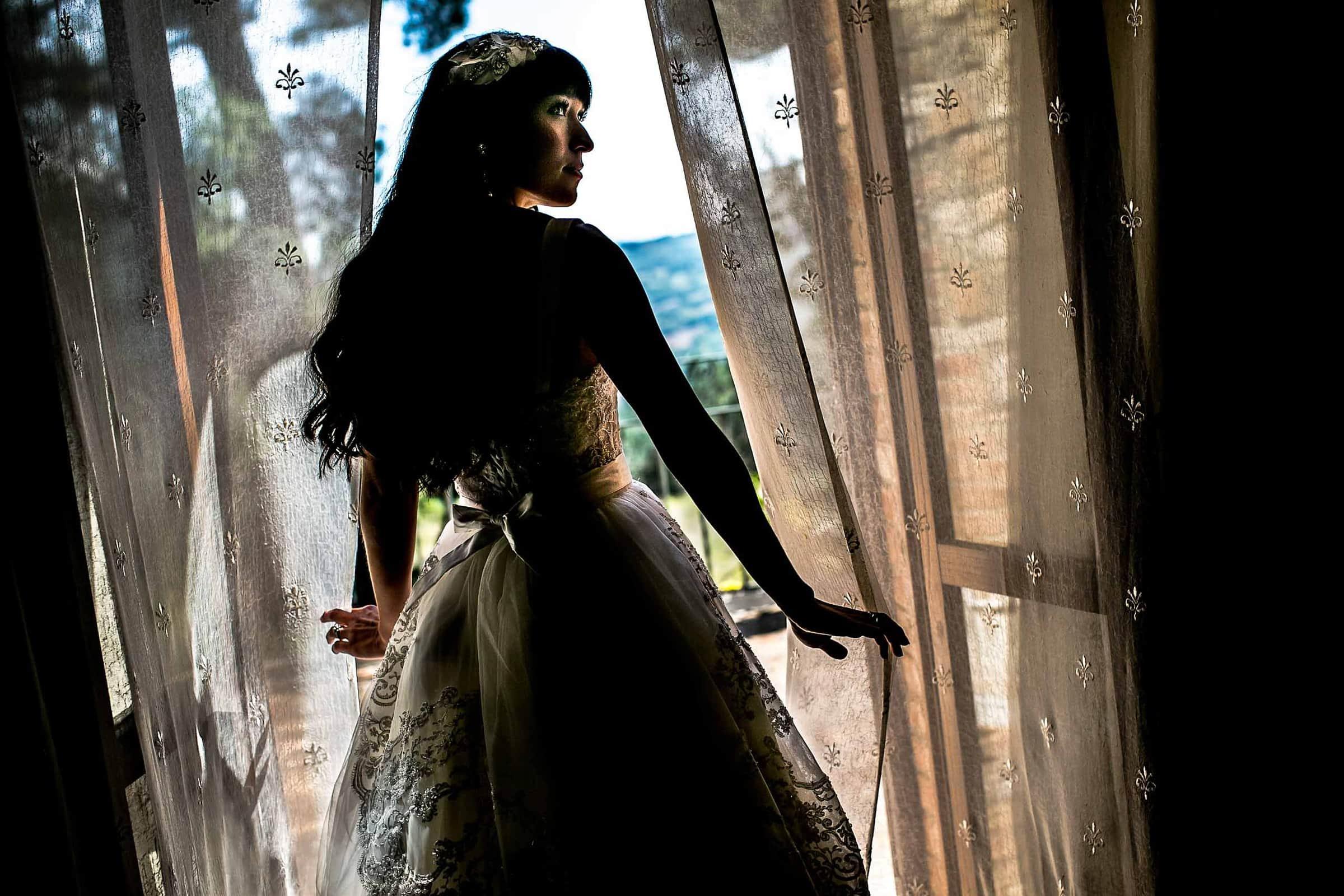 Portrait of a bride in a window moments before her Villa Tre Grazie Wedding in Umbria near Todi, Italy.