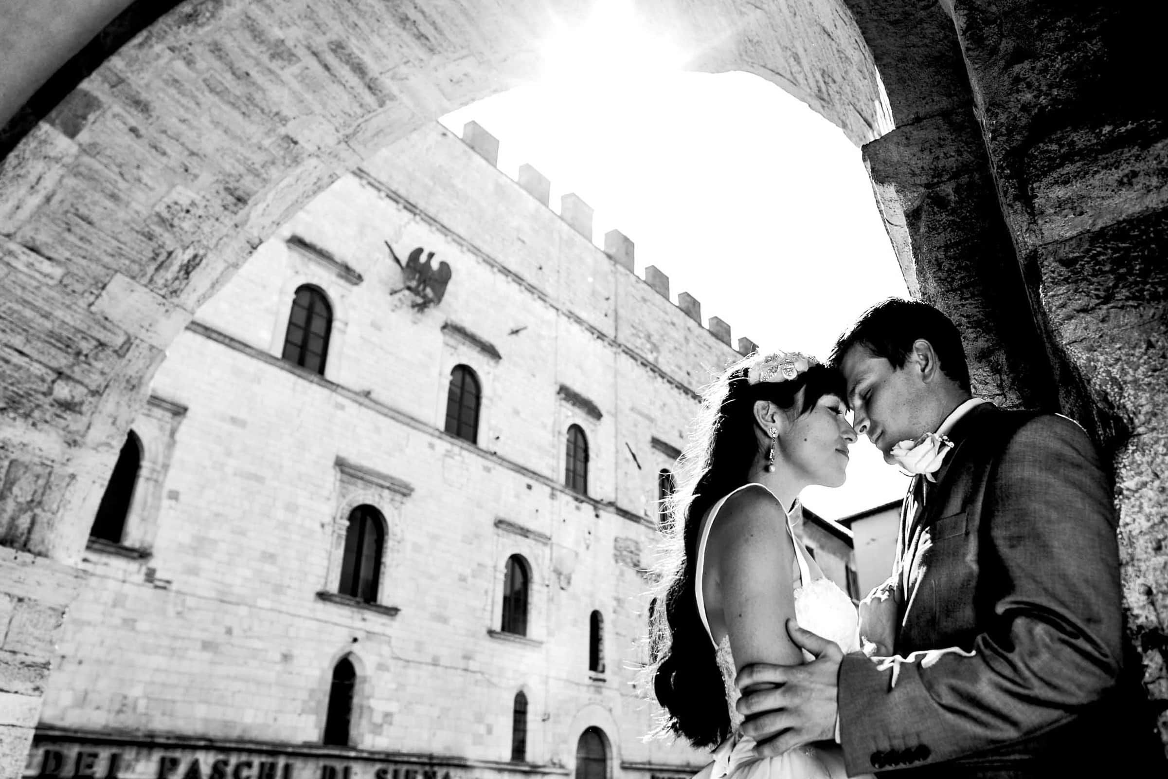 Bride and groom embracing each other in Todi before their Villa Tre Grazie Wedding in Umbria.