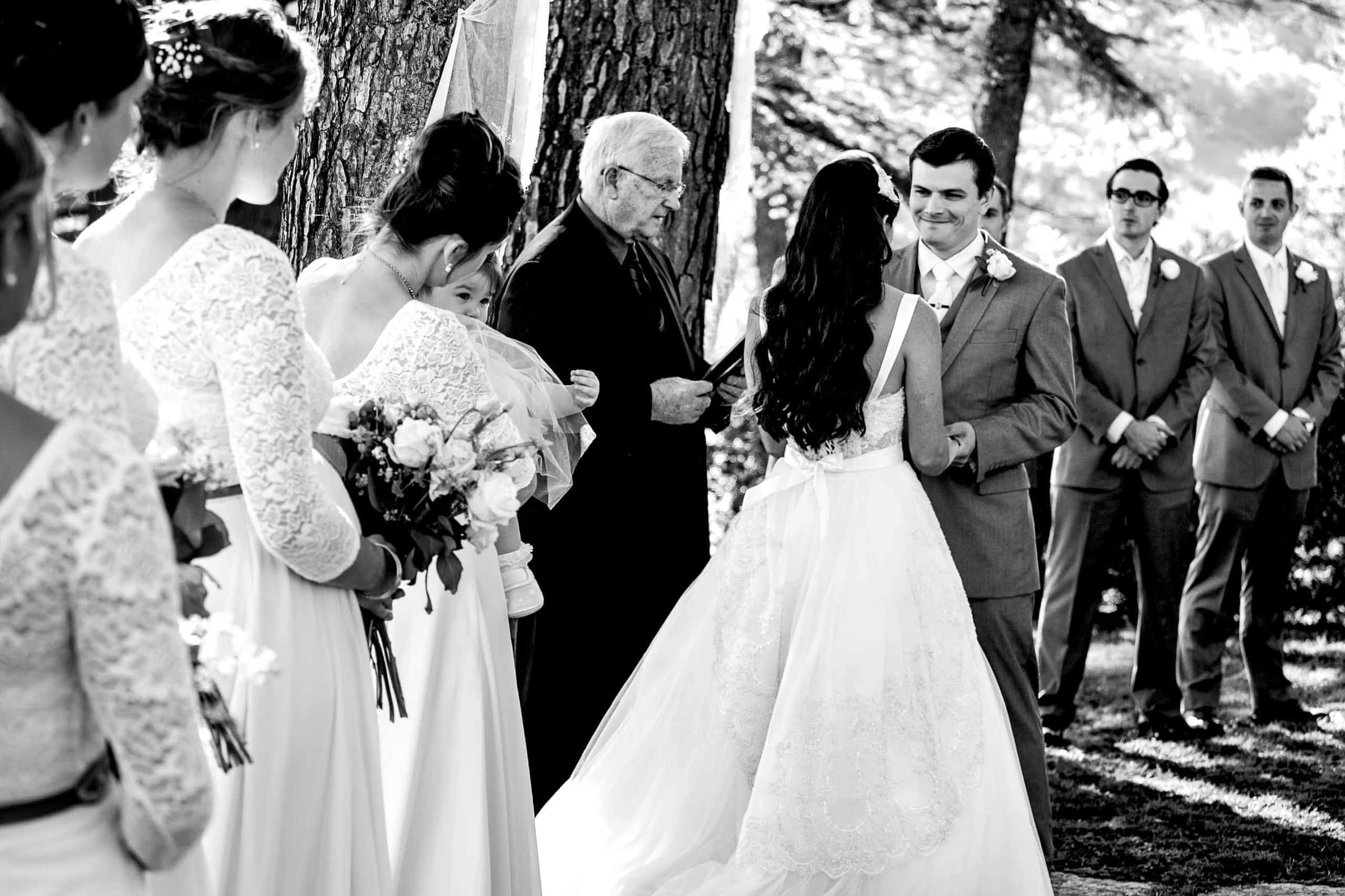 Black and white photo of a bride and groom exchanging vows during their Villa Tre Grazie wedding ceremony near Todi, Italy in Umbria.