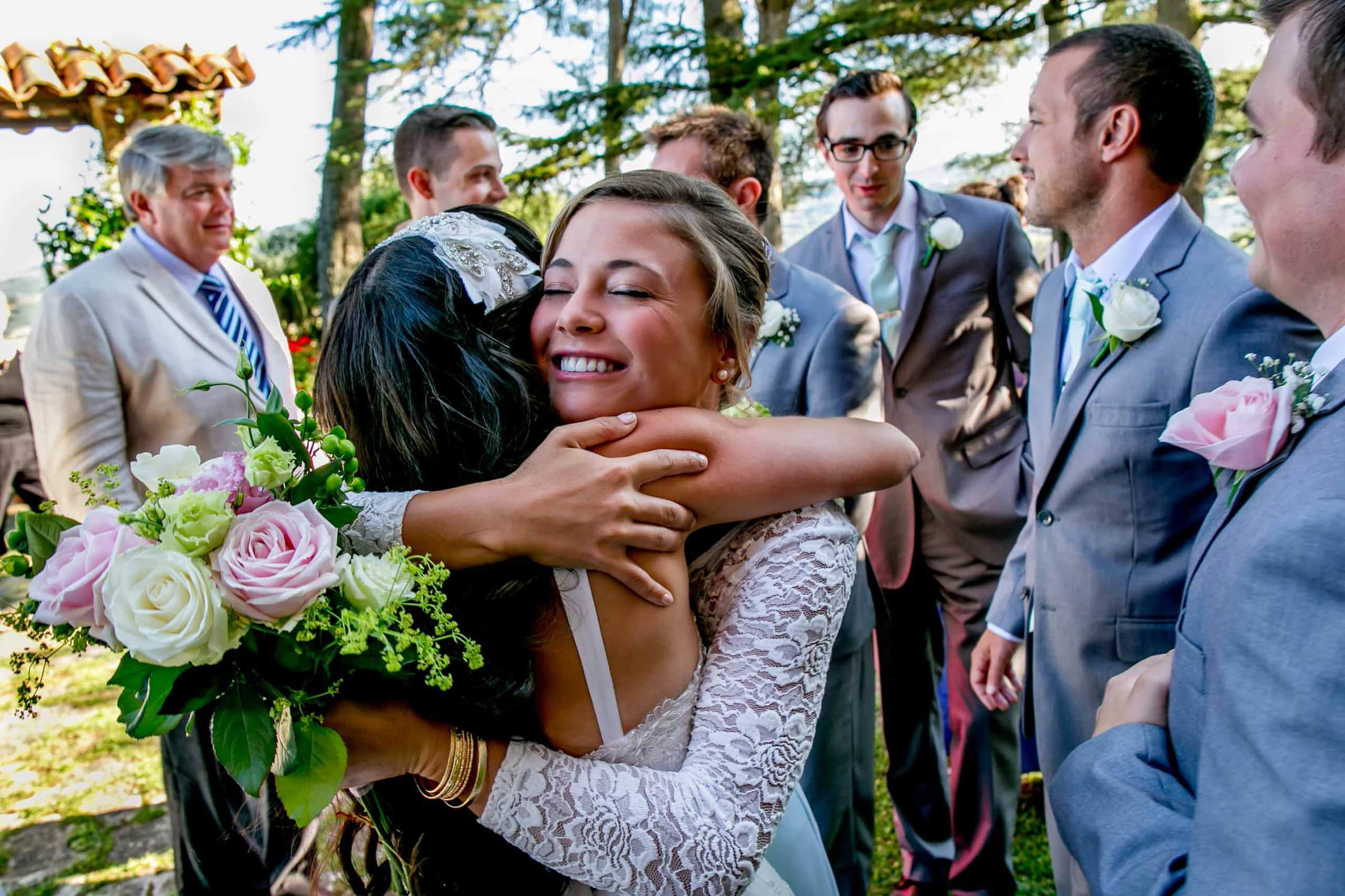 Bride hugging her best friend moments after her Villa Tre Grazie wedding ceremony near Todi, Italy in Umbria.