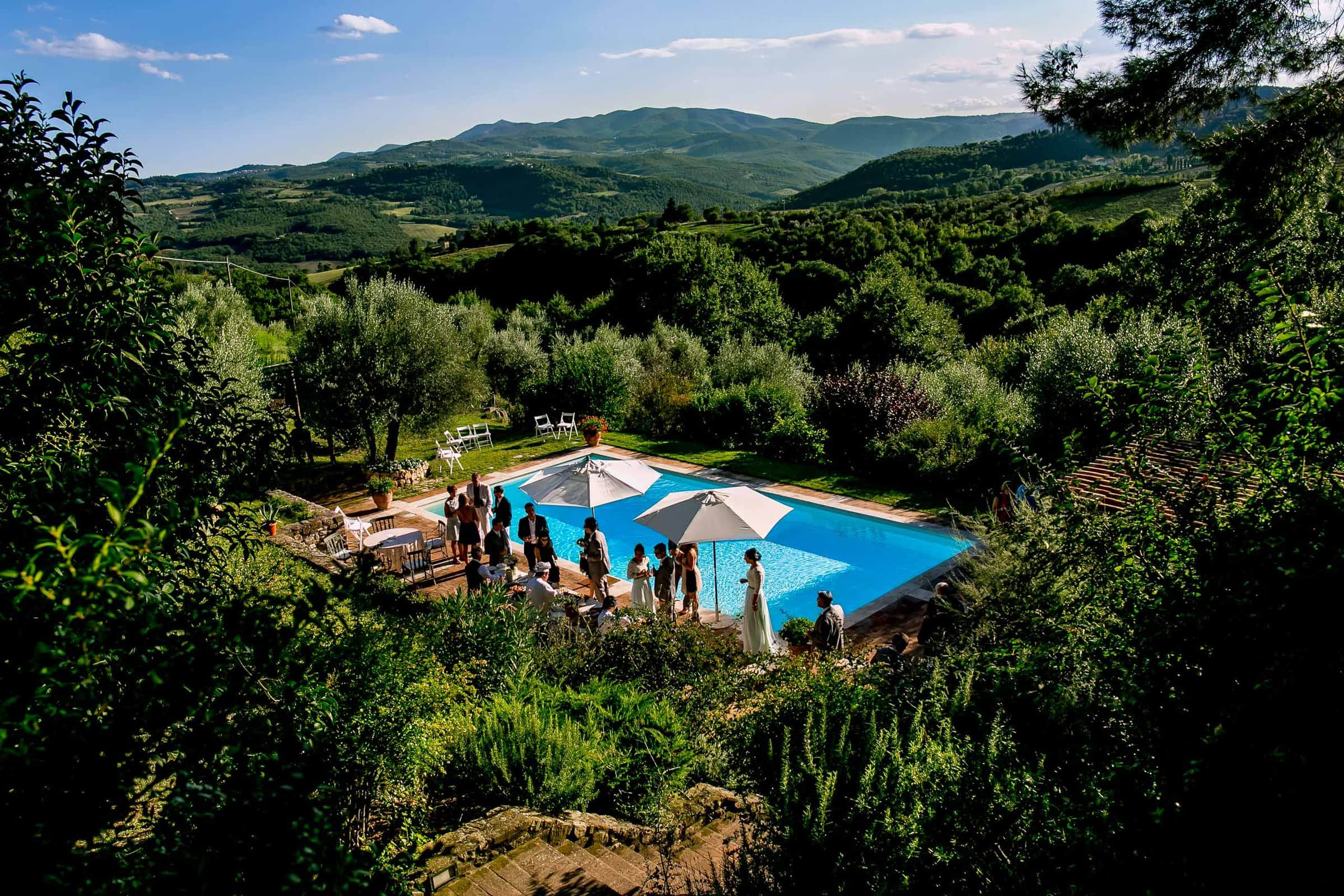 Pool party with family, friends and the bride and groom moments after a gorgeous Villa Tre Grazie wedding ceremony near Todi, Italy in Umbria.