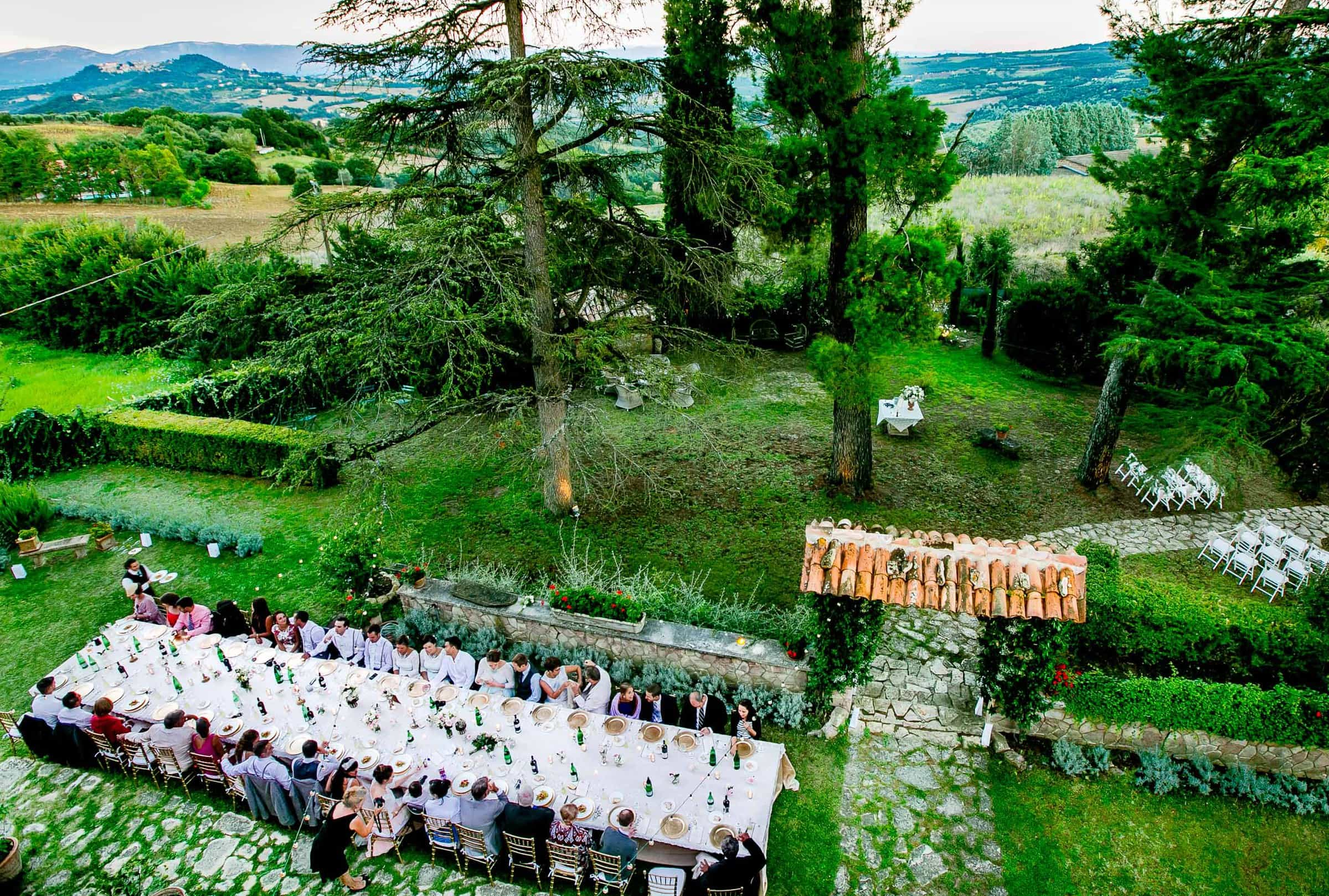 Wide angle view of a massive dinner table during a Villa Tre Grazie wedding ceremony near Todi, Italy in Umbria.