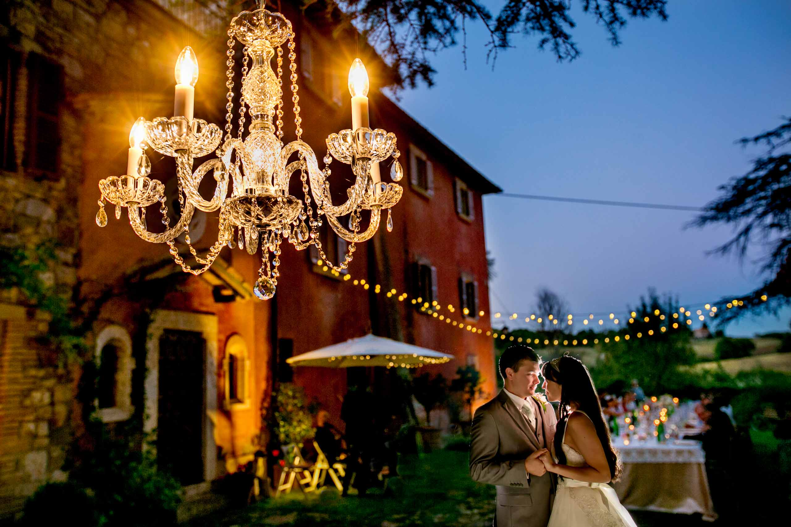 Bride and groom embracing under a chandelier during a Villa Tre Grazie wedding ceremony near Todi, Italy in Umbria.
