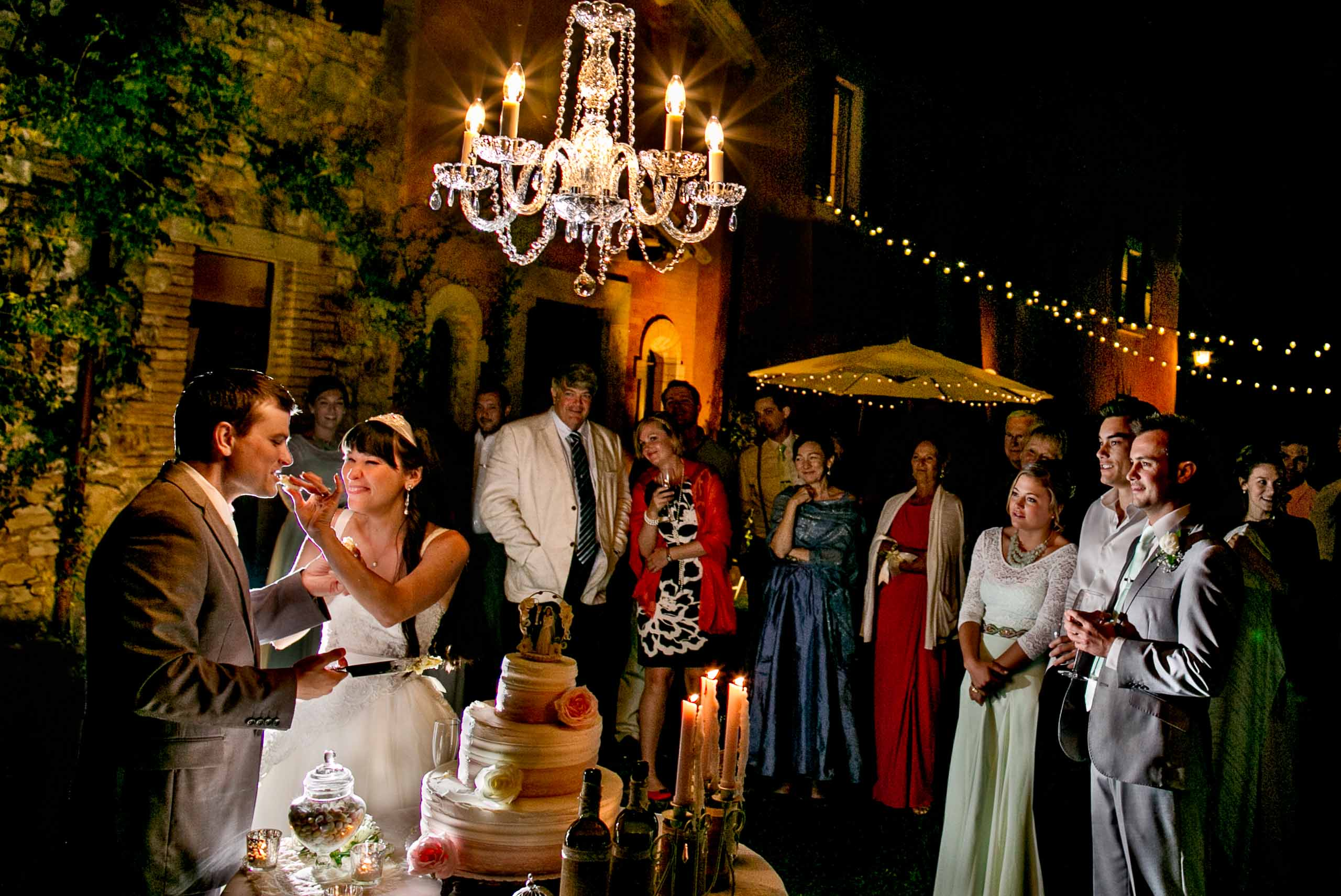 Bride and groom having fun eating their cake at a Villa Tre Grazie wedding near Todi, Italy in Umbria.
