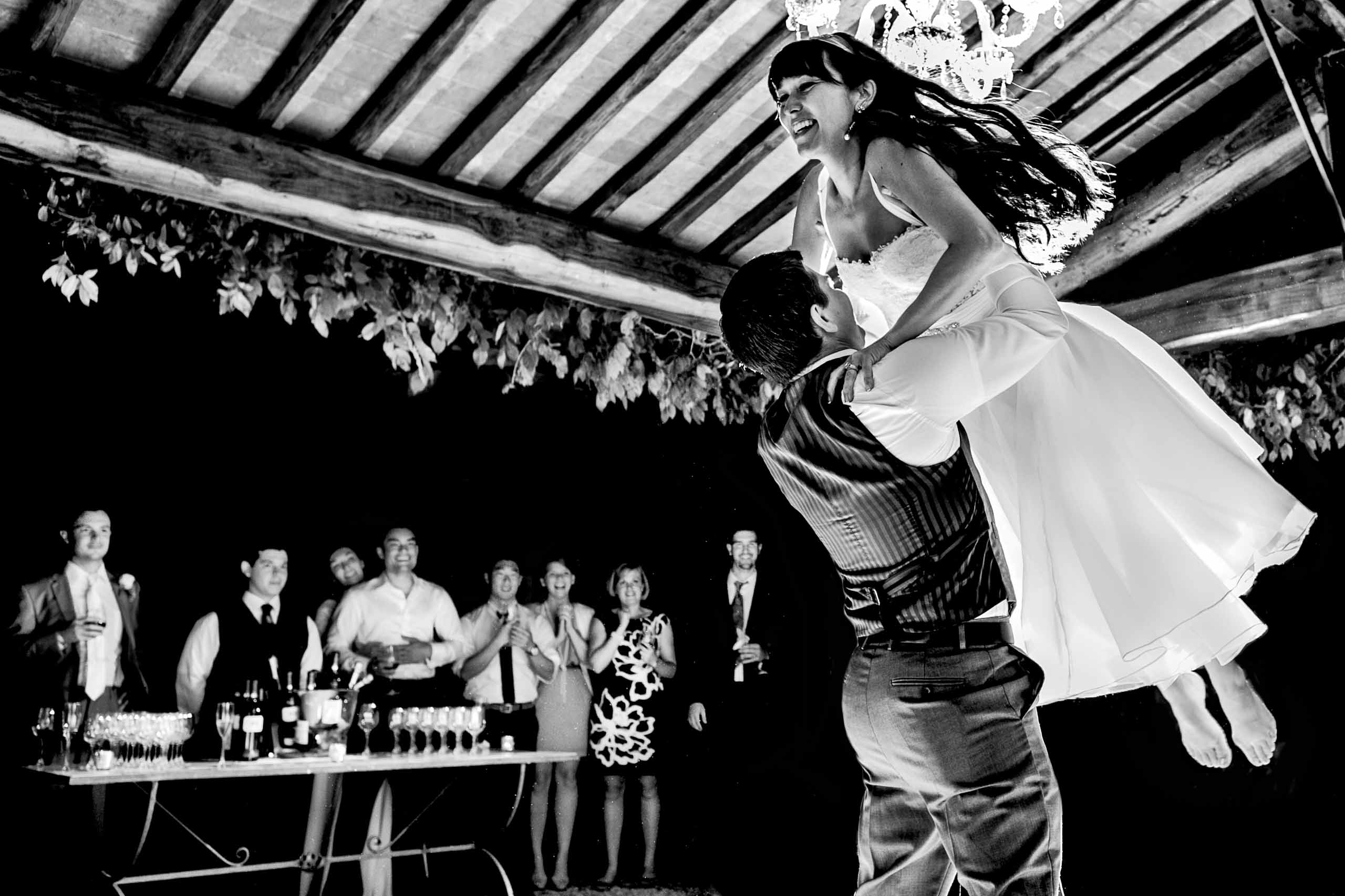 First dance with groom carrying bride over his head during their Villa Tre Grazie wedding reception near Todi, Italy in Umbria.