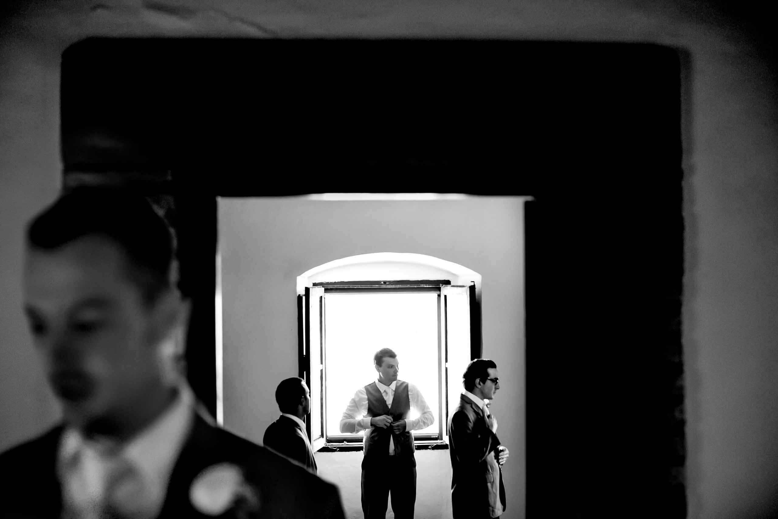 Groom in a window getting ready for a Villa Tre Grazie Wedding in Umbria near Todi, Italy.