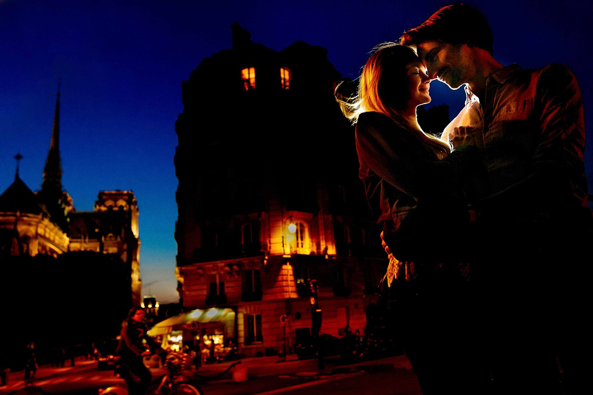 Lovers in Paris during blue hour with warm backlight wrapping around them. Engagement photo by Jos and Tree.