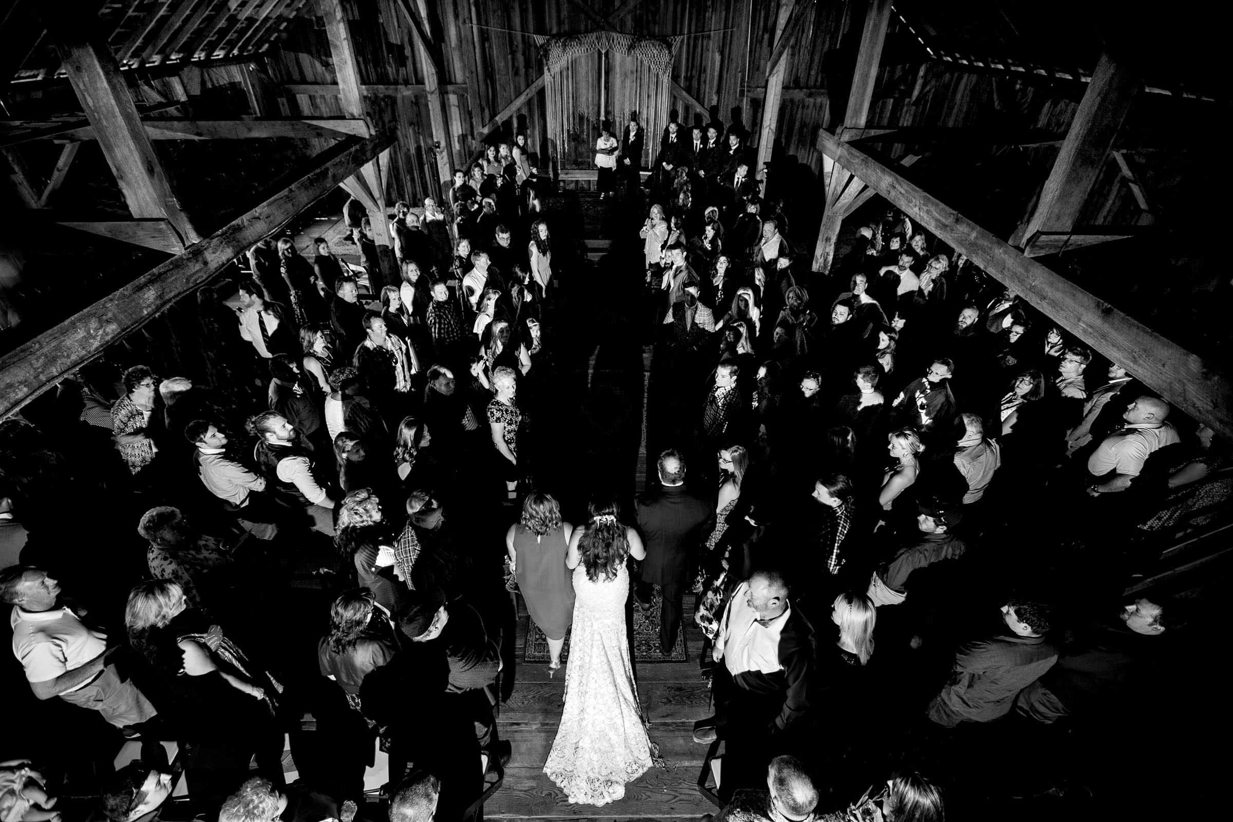 Bride walking into her Ohana Barn wedding amidst a vast room of guests in Corvallis, Oregon
