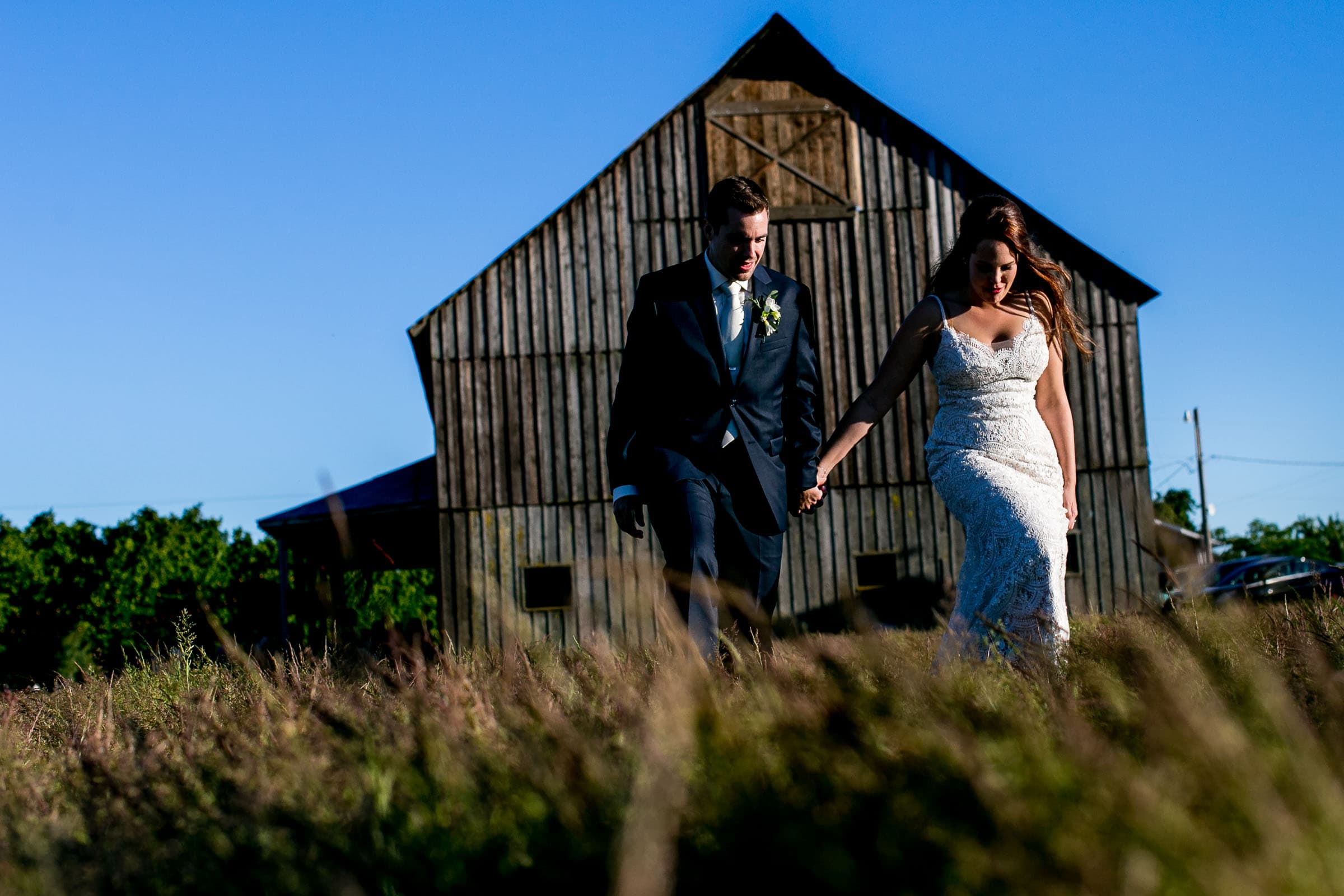 Bride and groom walking in the fields enjoying sunset during their Ohana Barn wedding day.