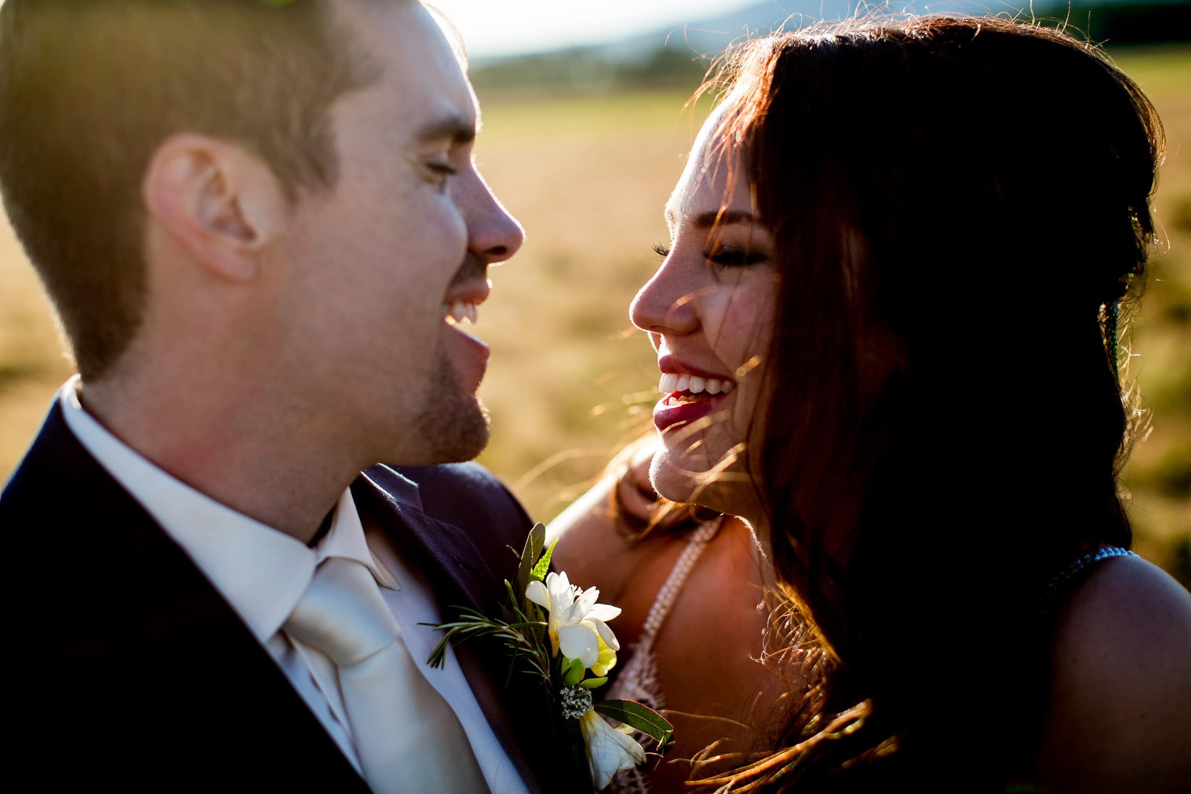 Bride and groom laughing together in the fields enjoying sunset during their Ohana Barn wedding day.