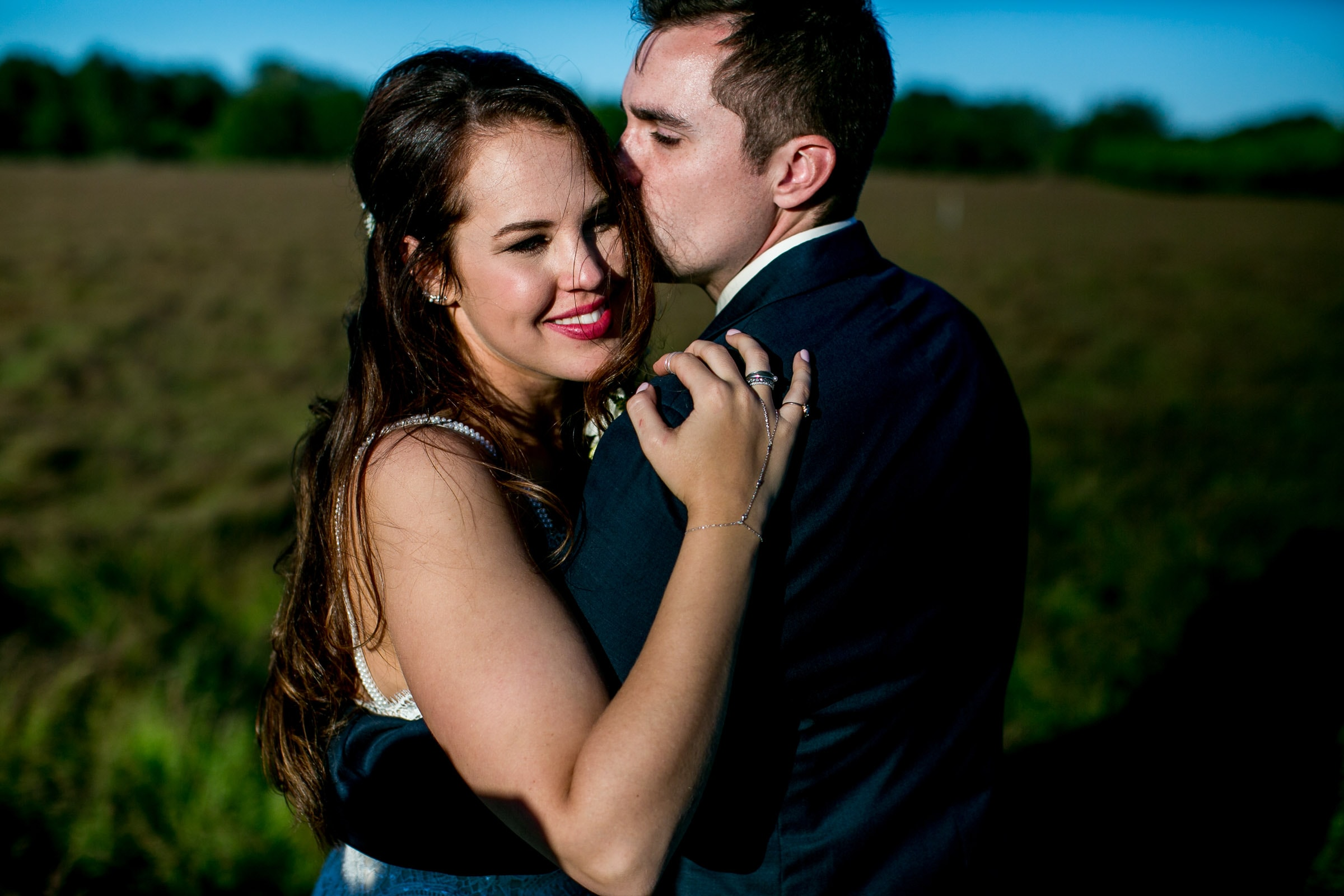 Bride and groom embracing together in the fields enjoying sunset during their Ohana Barn wedding day.