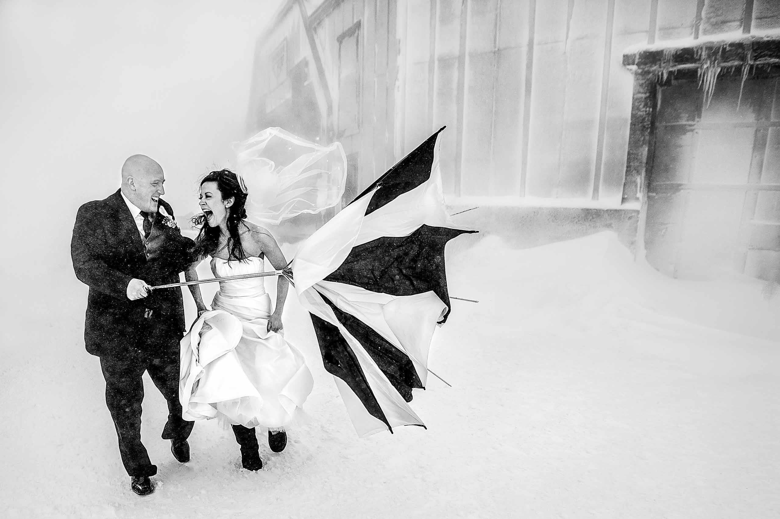 Ecstatic couple running in the snow and wild wind with their umbrella inverted. Captured atop Mt Hood near Silcox Hut. Award winning wedding photo by Fearless Photographers