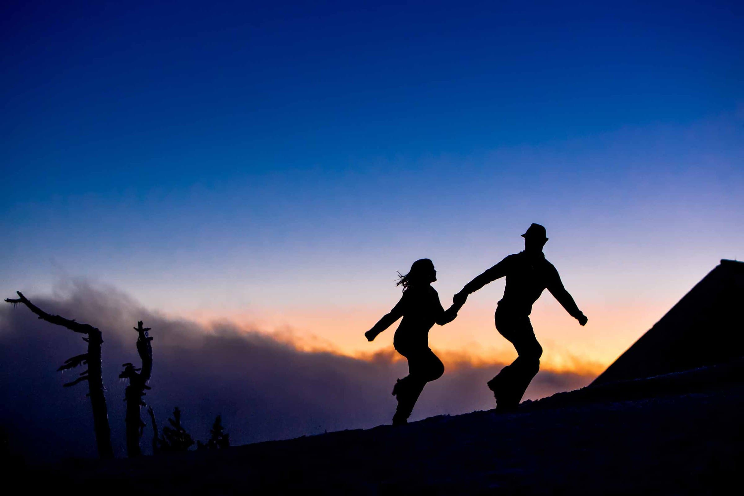 A dynamic photo of a couple running up the hill at Timberline Lodge for location number one of their Oregon engagement photos