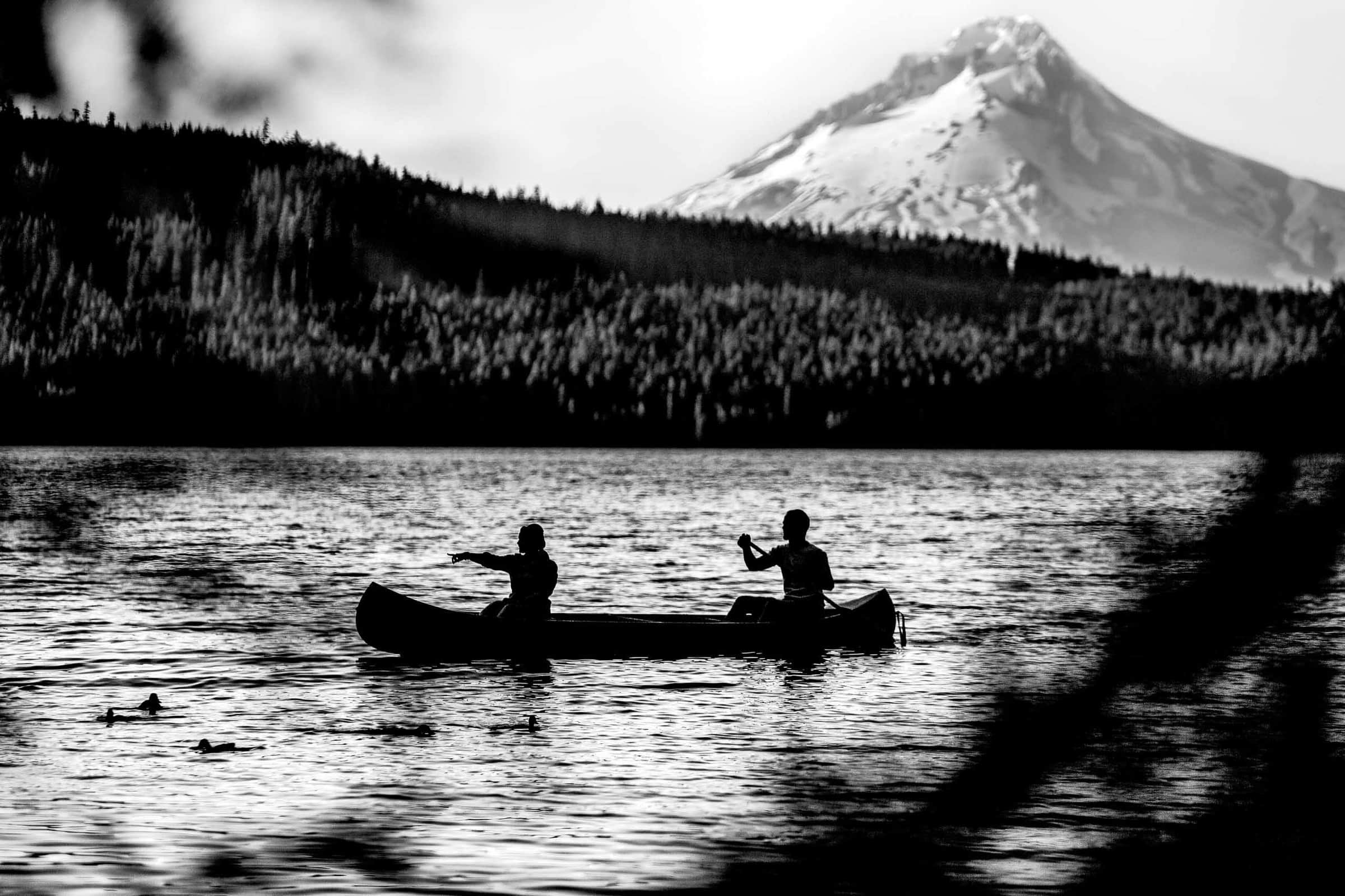 A fantastic silhouette photo of a couple canoeing at Timothy lake with Mt Hood in the background for their Oregon engagement photos