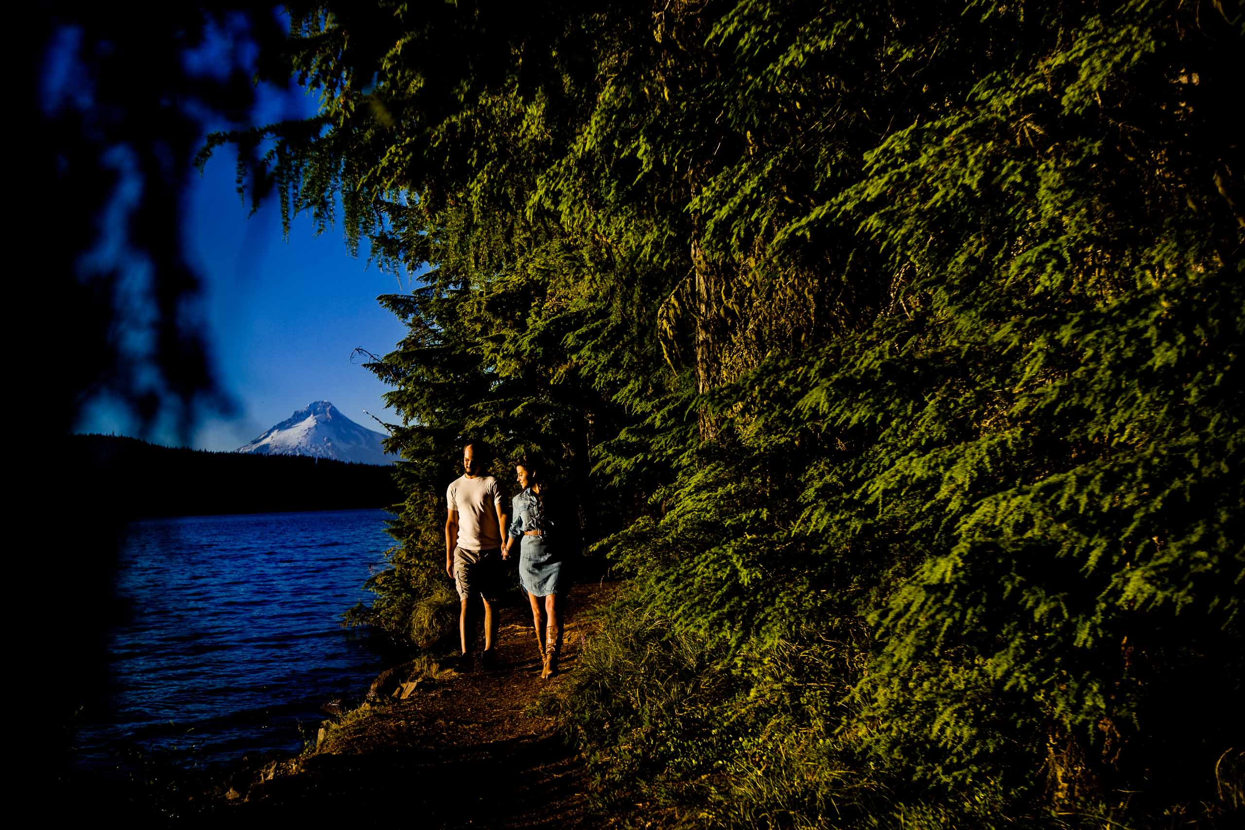 A couple walking along the Timothy Lake water with Mt Hood in the backdrop for their Oregon engagement photos