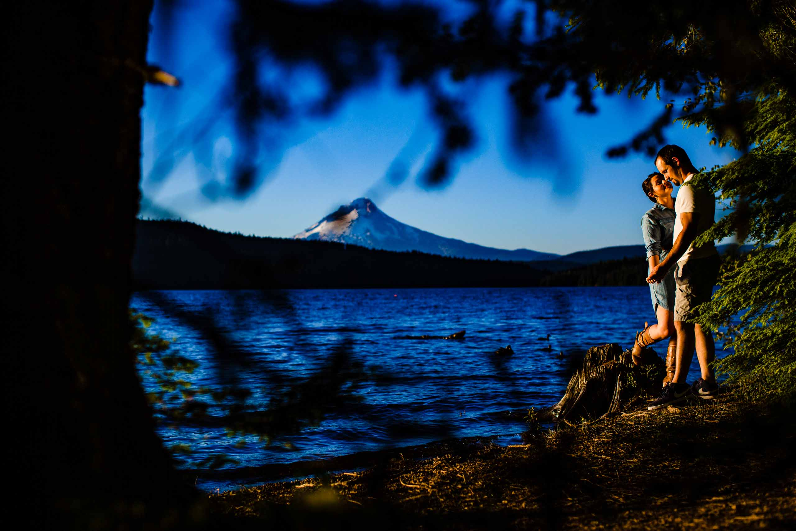 A couple holding each other near the water at Timothy Lake with Mt Hood in the distance for their Oregon engagement photos