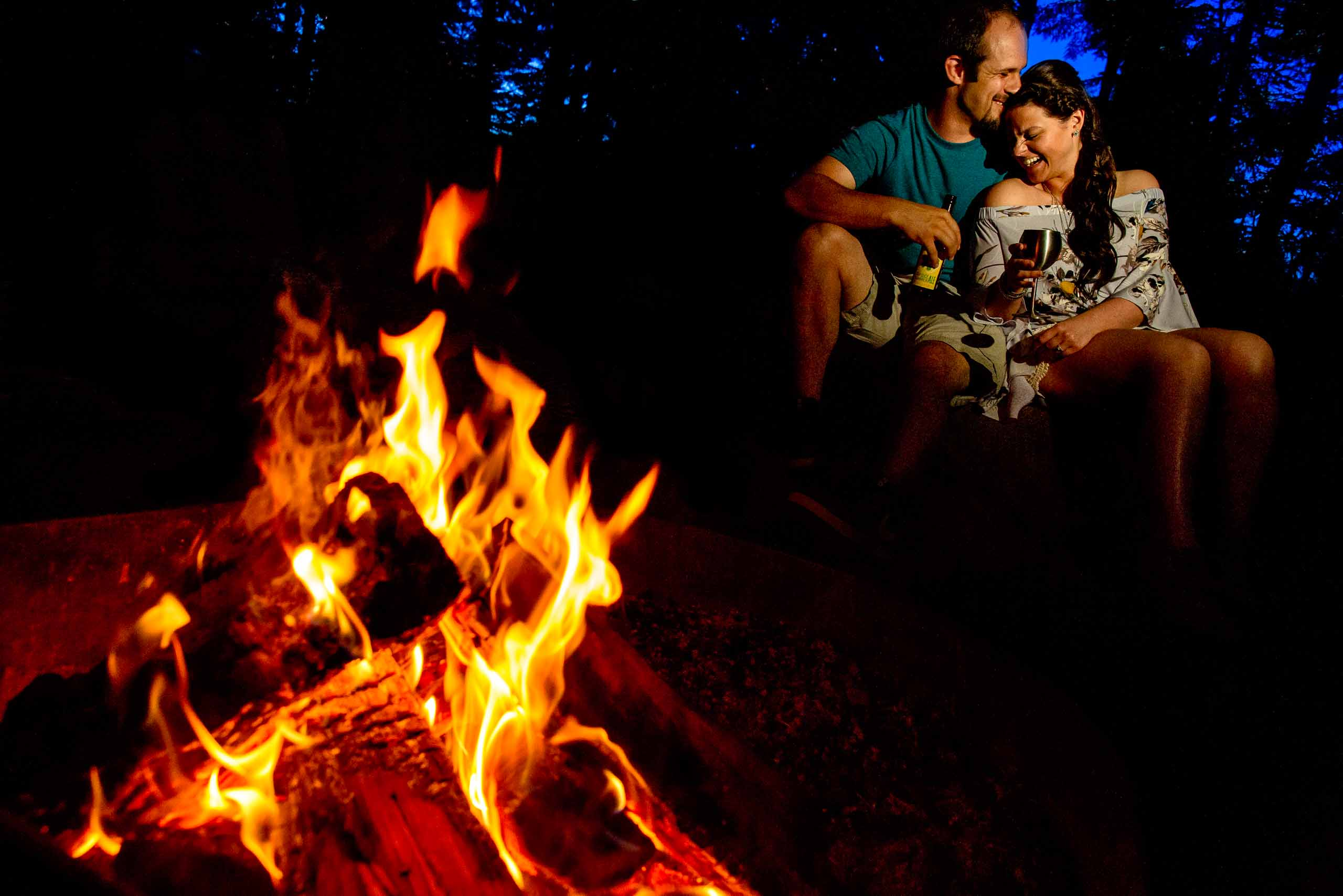 A couple laughing together holding beers near a camp fire for their Oregon engagement photos