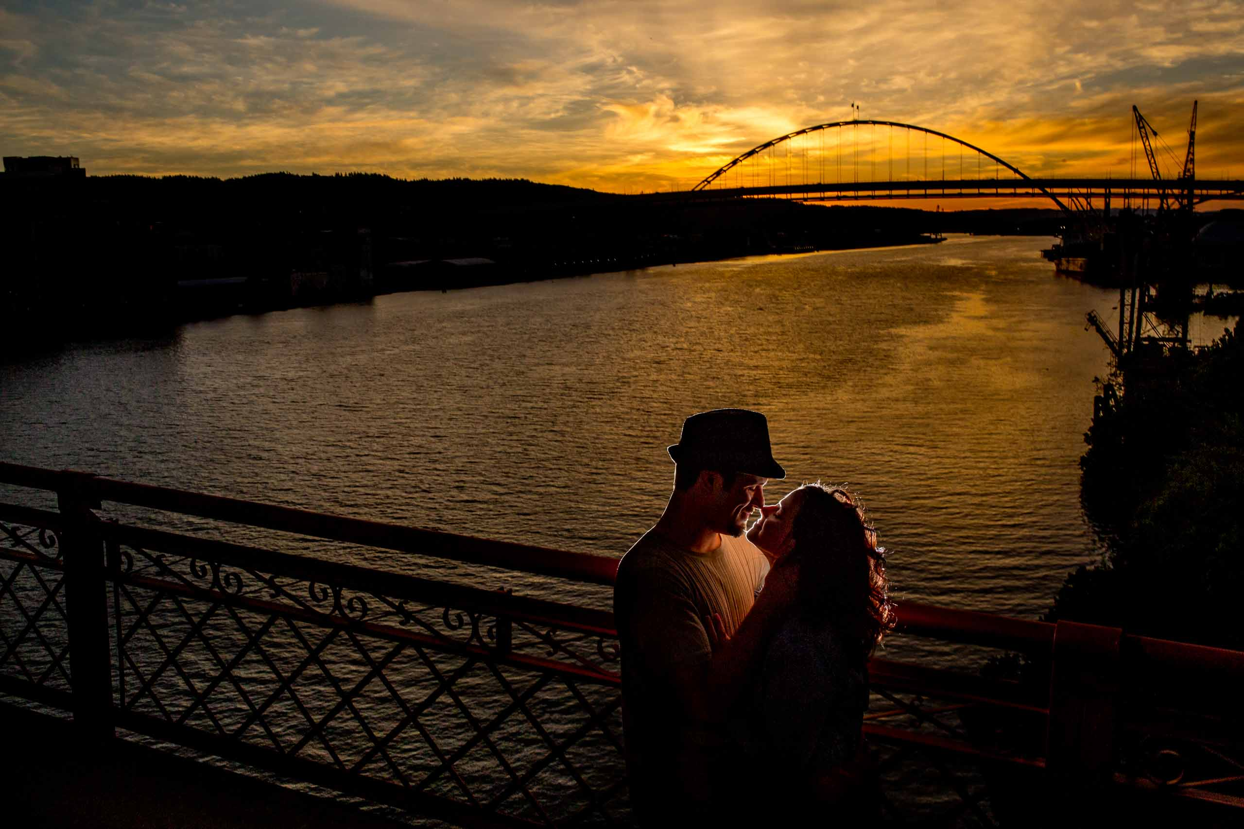 An intimate back lit warm photo of a couple on Portland's broadway bridge for their Oregon engagement photos