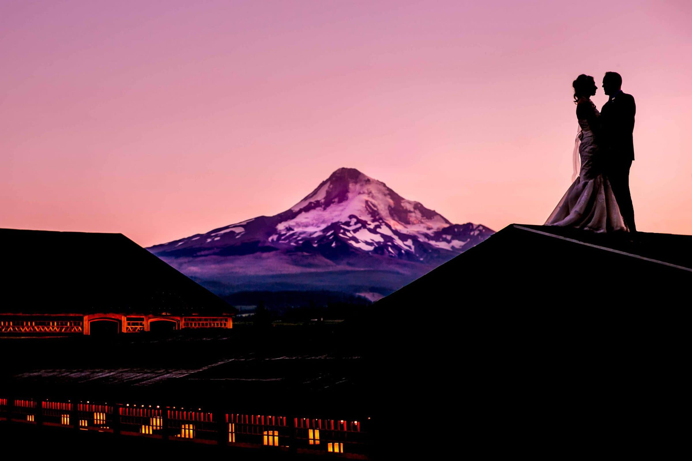 Epic silhouette of bride and groom on rooftop looking out over Mt Hood Organic Farms