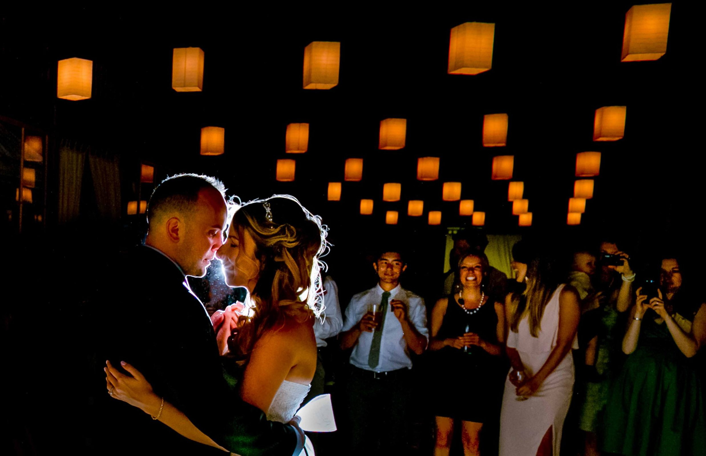 Beautiful first dance photo of a bride and groom with guests and warm lights during their Mt Hood Organic Farms wedding reception in Hood River, Oregon