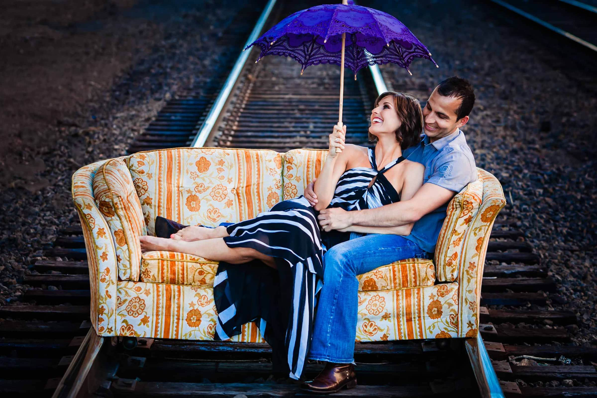 Gorgeous Portland engagement photo of a couple on railroad tracks on a couch super happy and madly in love