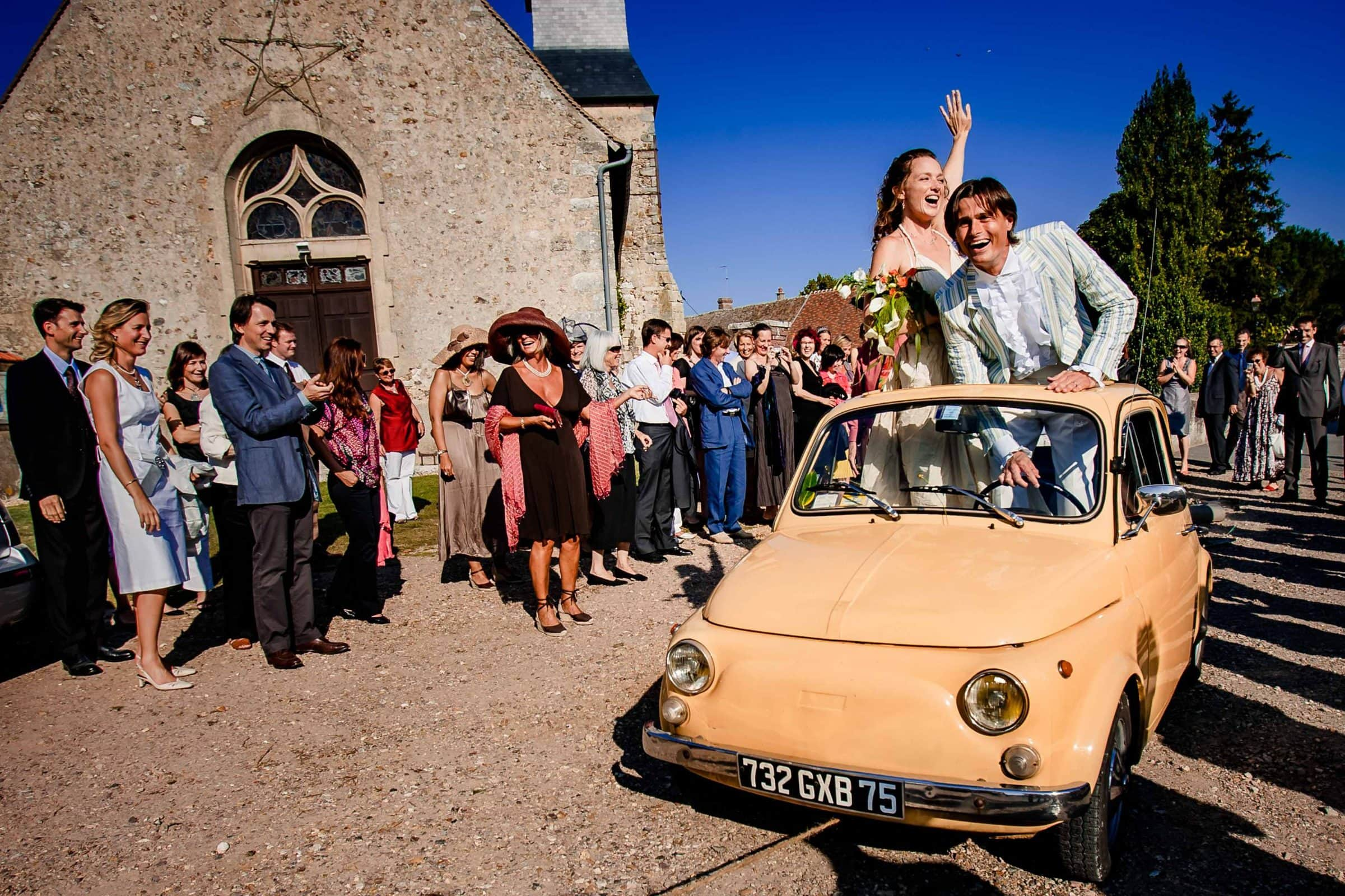 bride and groom exiting in small French car from their ceremony in Normandy France